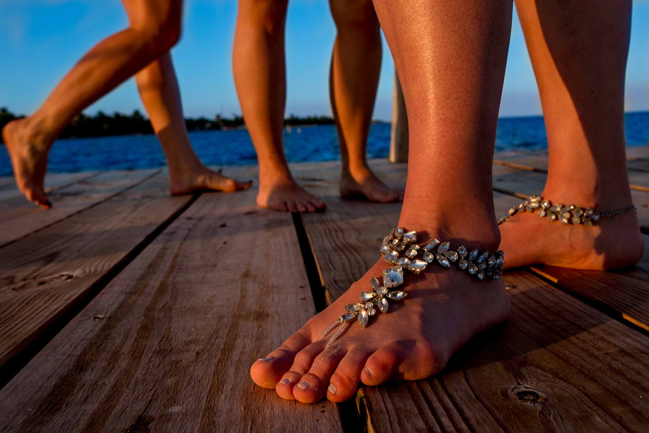 Bridesmaids feet on a dock at sunset the day before Nikki and Paul's Portofino Beach Resort wedding in Belize