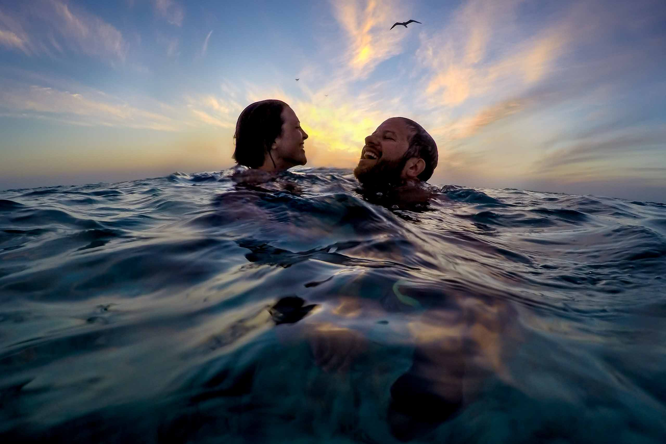 Bride and groom swimming in the ocean at sunset during their catamaran cruise the day before their Portofino Beach Resort wedding in Belize