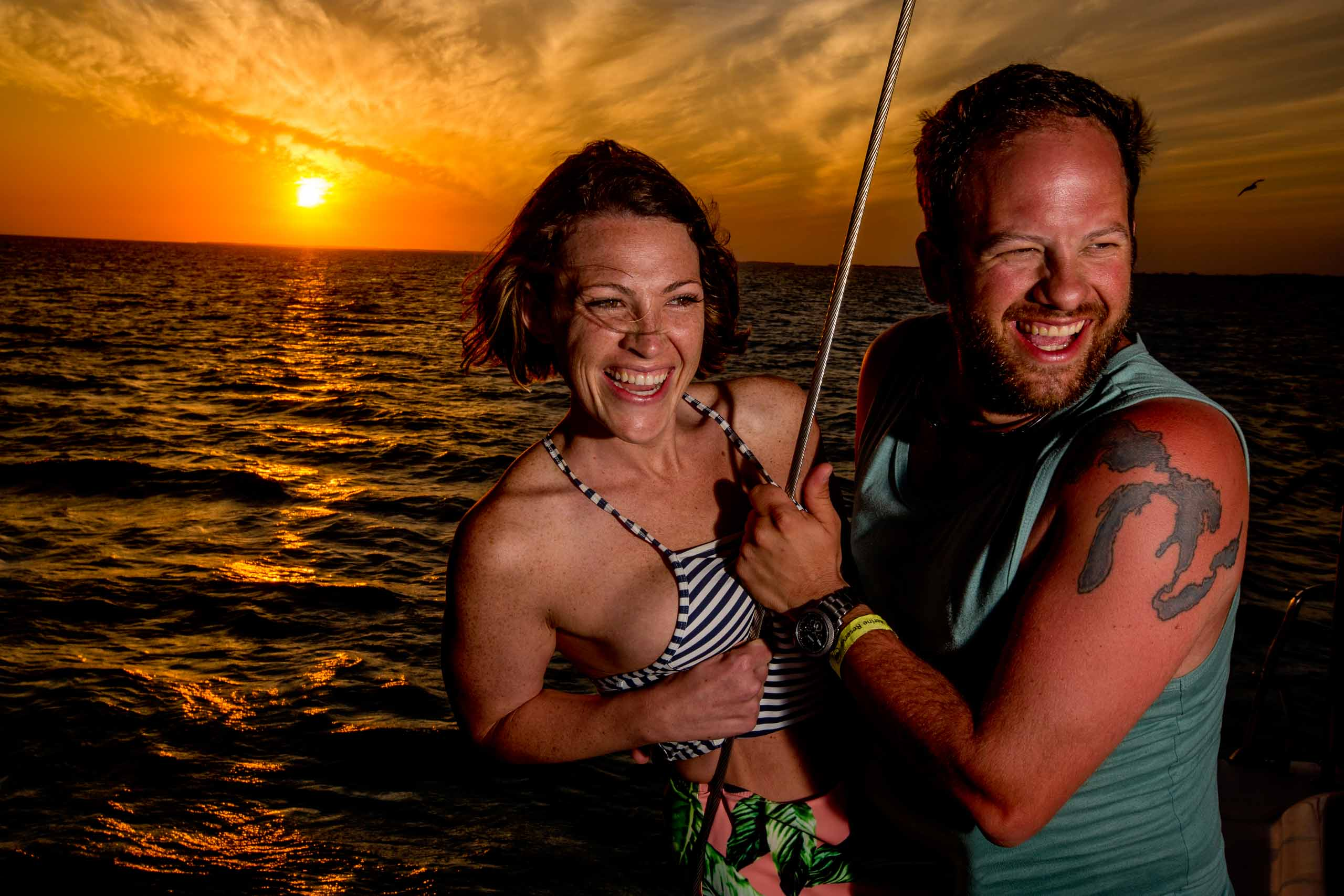 Bride and groom enjoying a sunset catamaran cruise the day before their Portofino Beach Resort wedding in Belize.