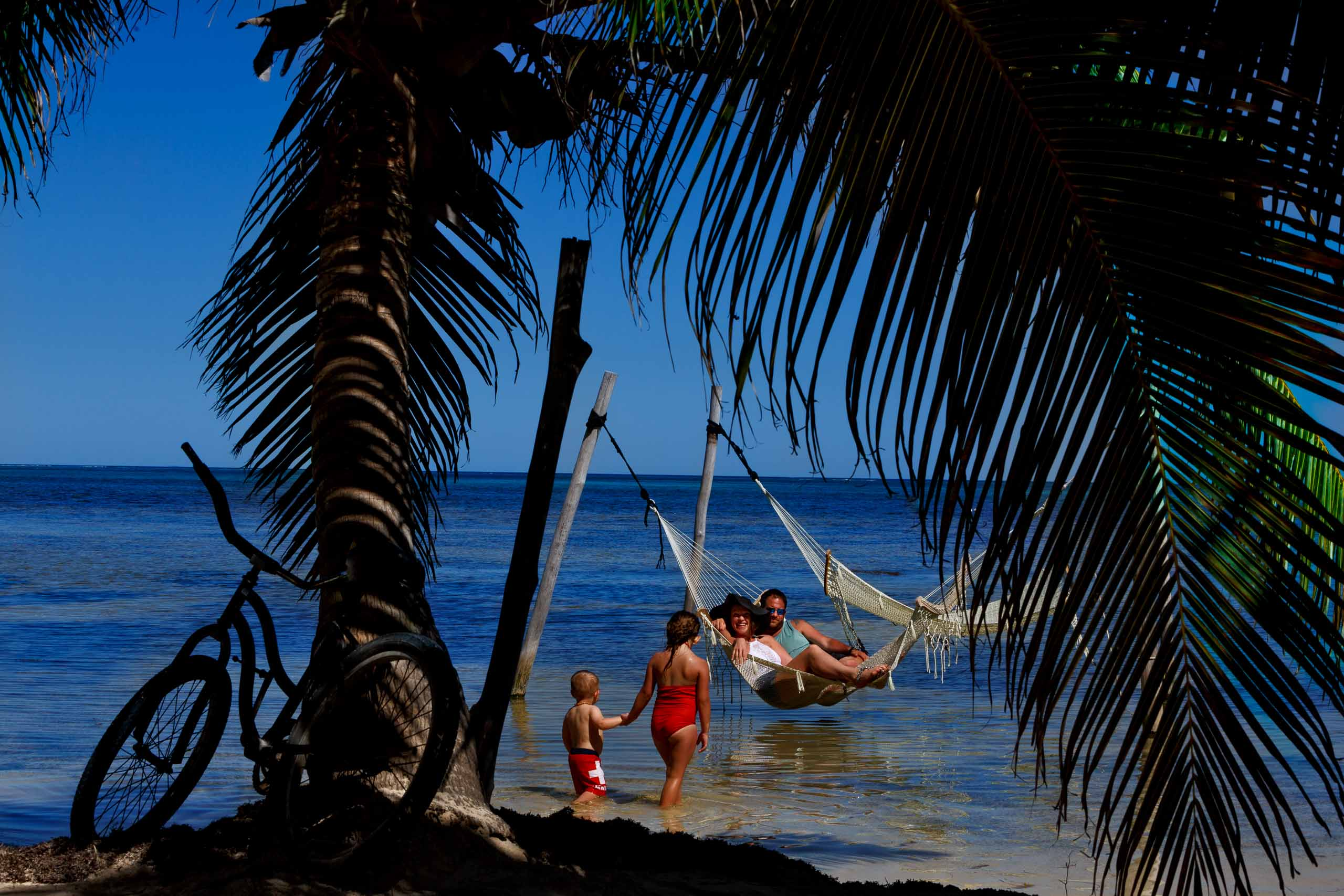 Bride and groom enjoying a hammock in the ocean the day before their Portofino Beach Resort wedding in Belize.