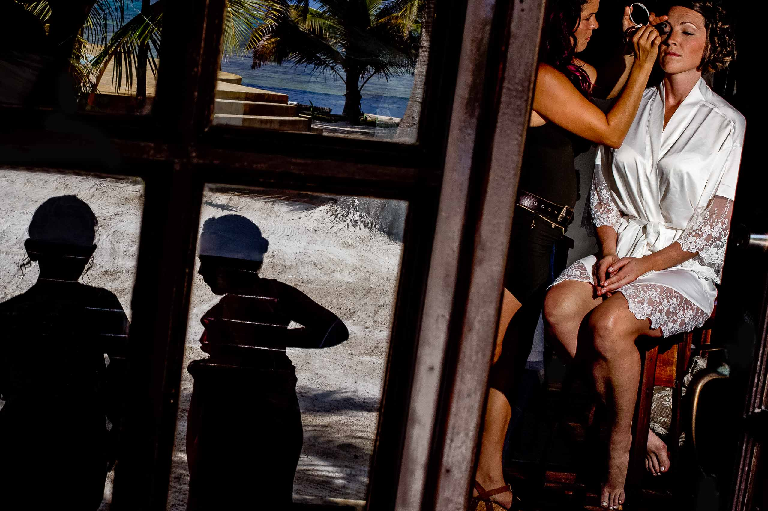 Bride getting ready with shadows of children on her Portofino Beach Resort wedding day