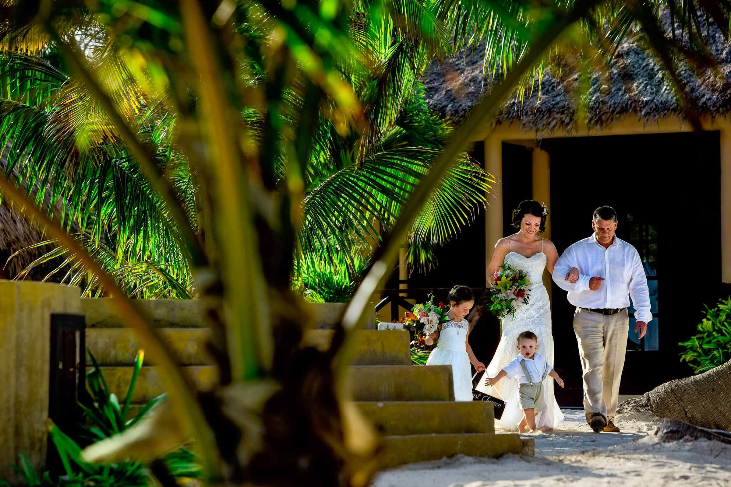 Bride walking into her Portofino Beach Resort wedding ceremony in Belize with father and children.
