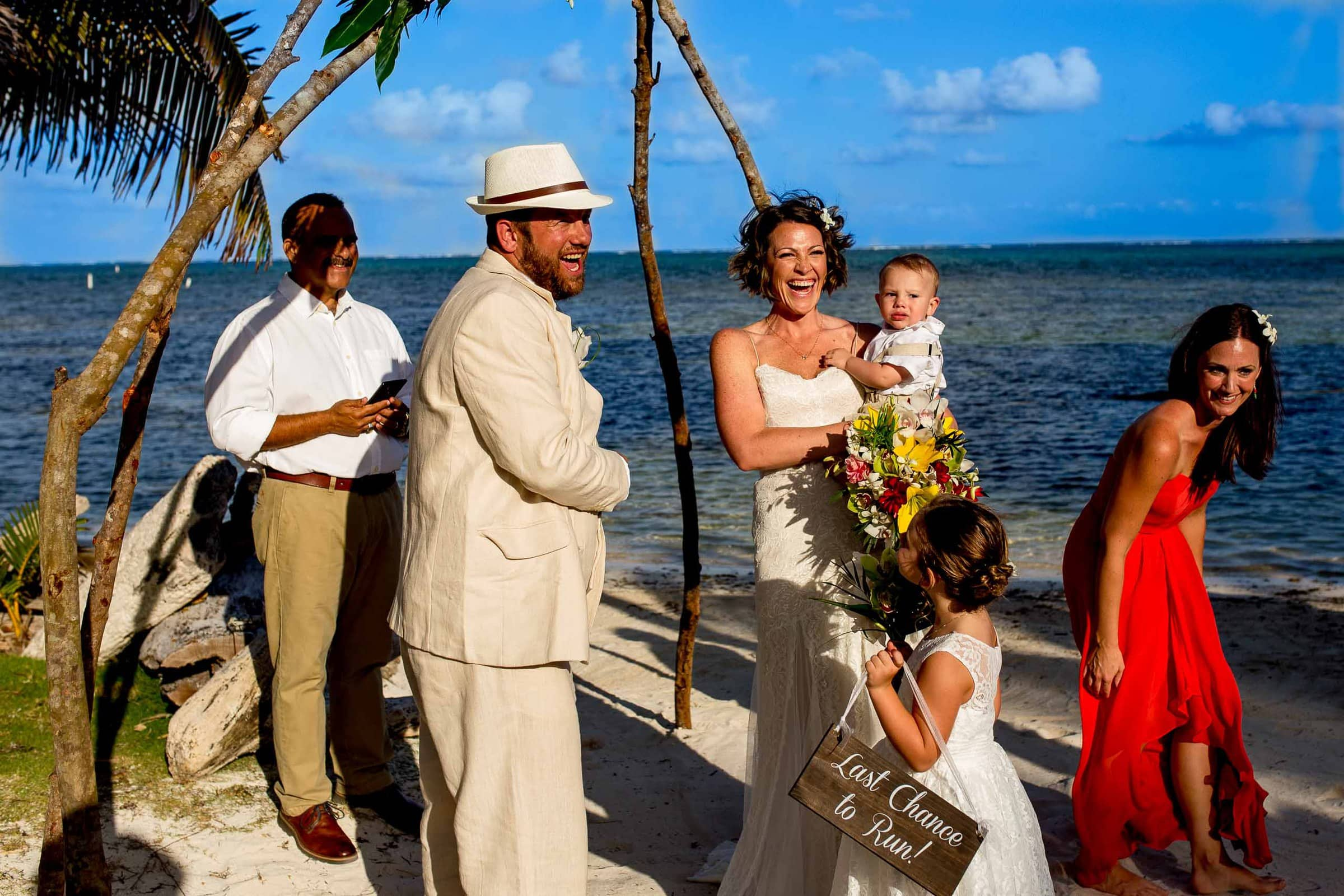 Bride and groom laughing during their Portofino Beach Resort wedding ceremony in Belize