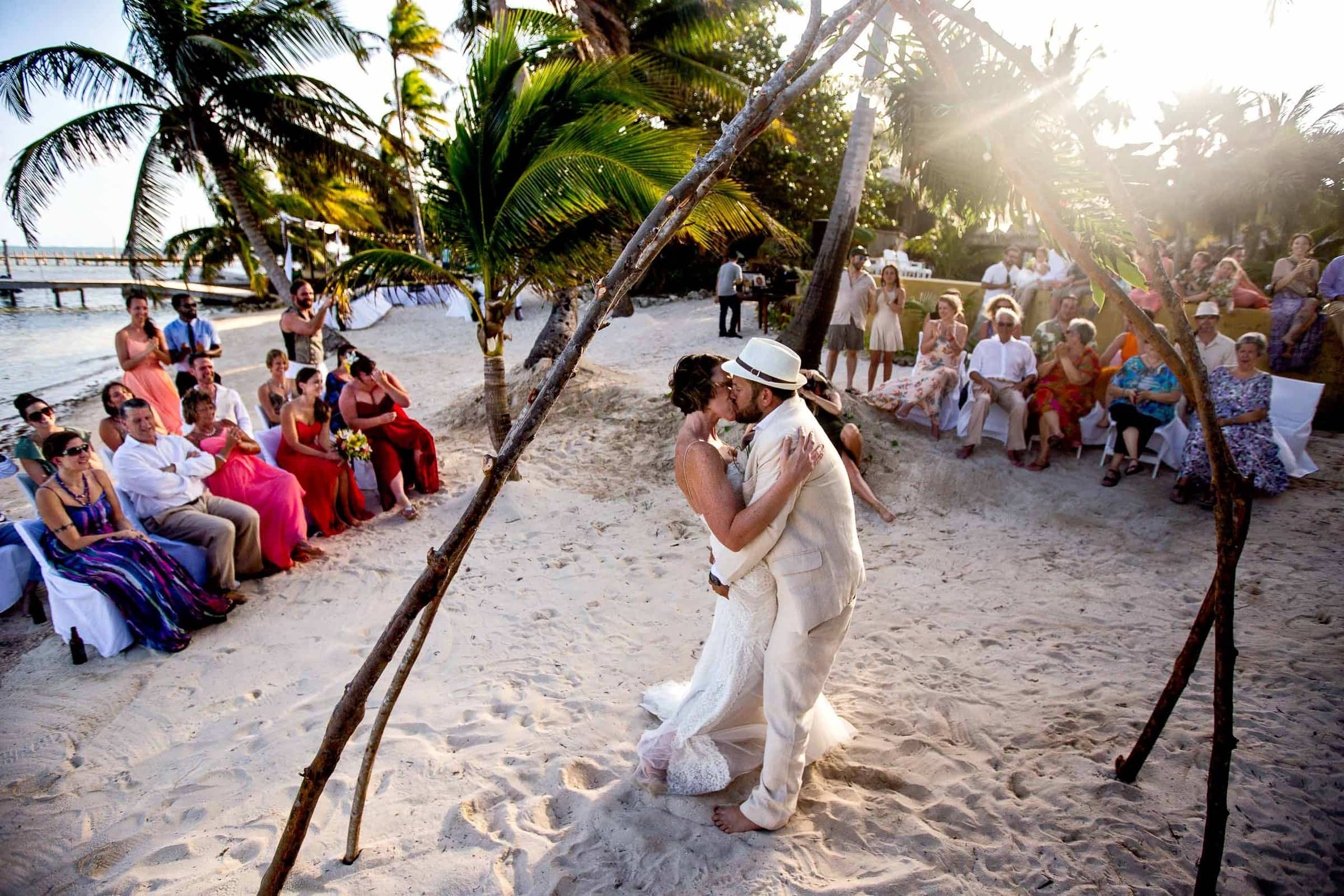 Bride and groom kiss during their Portofino Beach Resort wedding in Belize