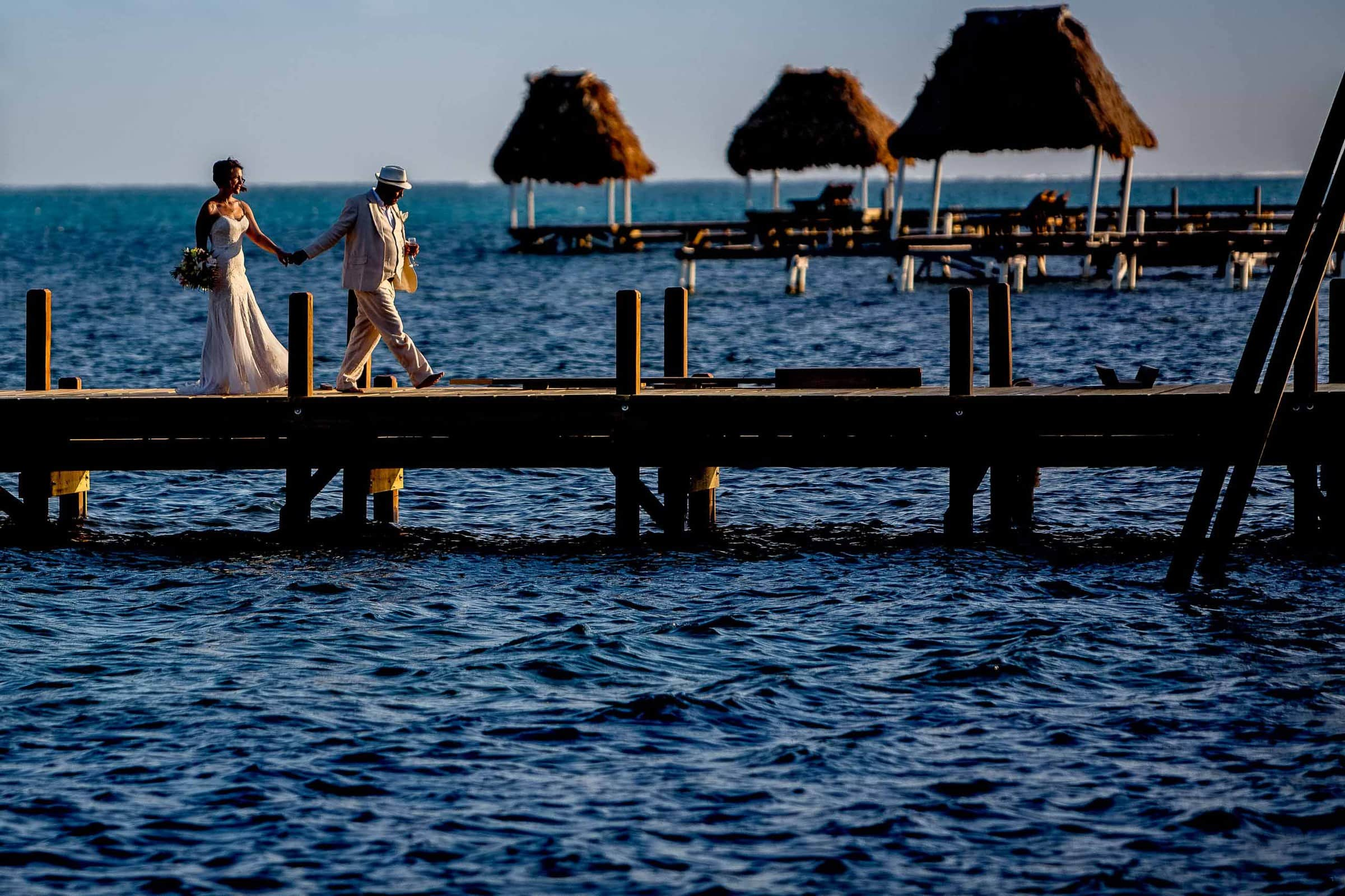 Bride and groom walking on the peer at sunset moments after their Portofino Beach Resort wedding ceremony in Belize