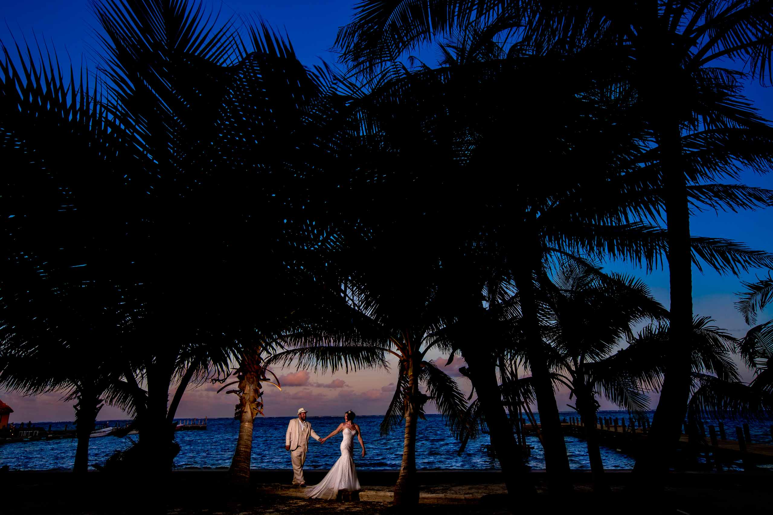 Beautiful sunset photo with purples and blues with the bride and groom during their Portofino Beach Resort wedding in Belize.