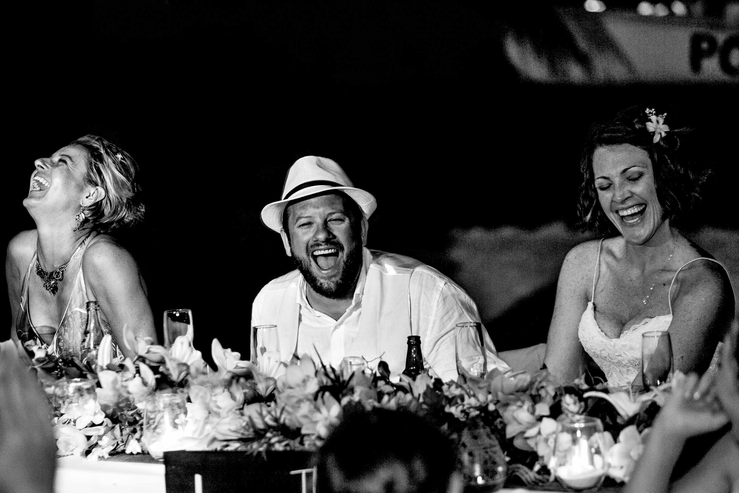 Bride and groom laughing with best friend during their Portofino Beach Resort wedding in Belize