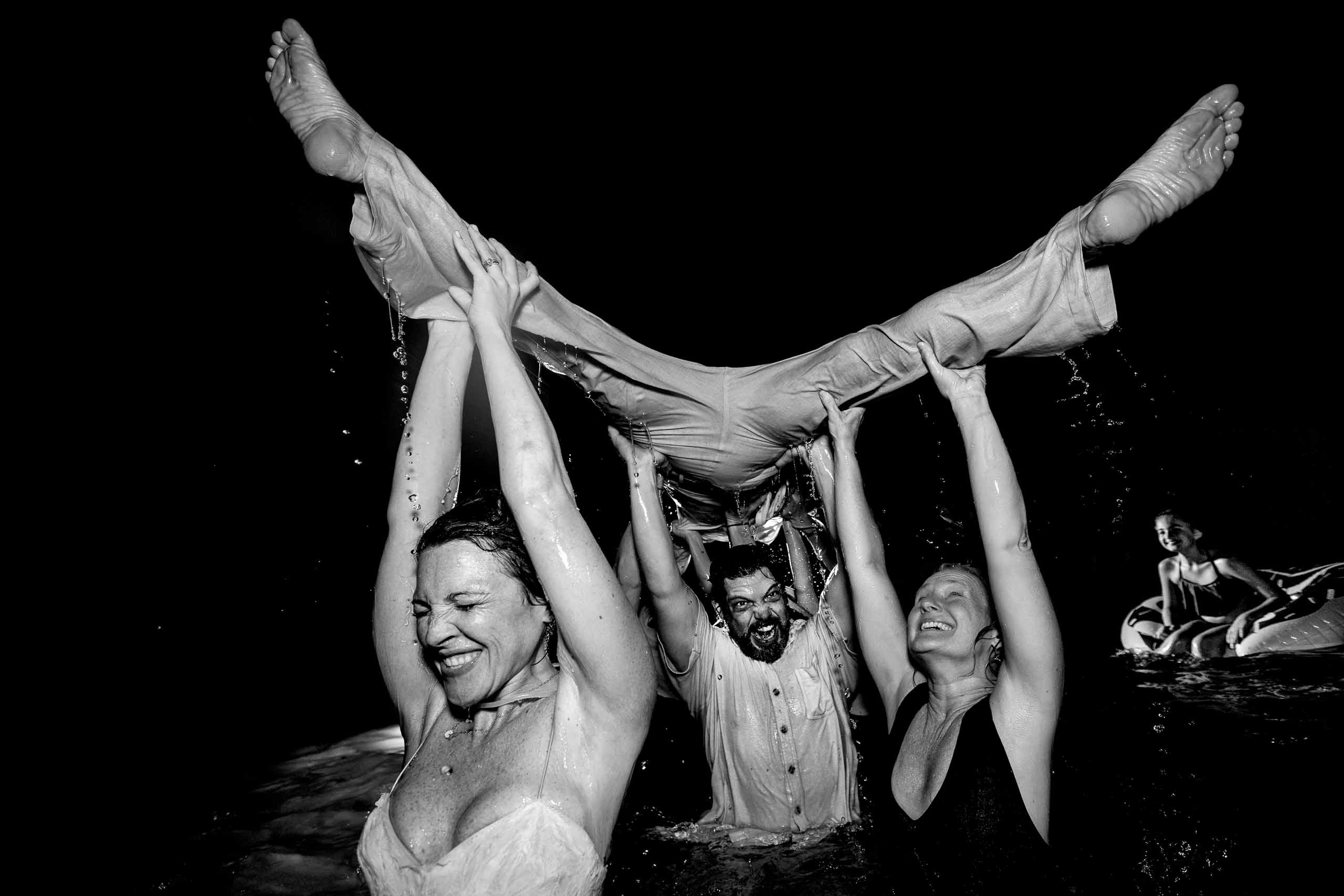 Crazy pool party photo of bride carrying groom in the air with water flying everywhere during their Portofino Beach Resort wedding reception in Belize