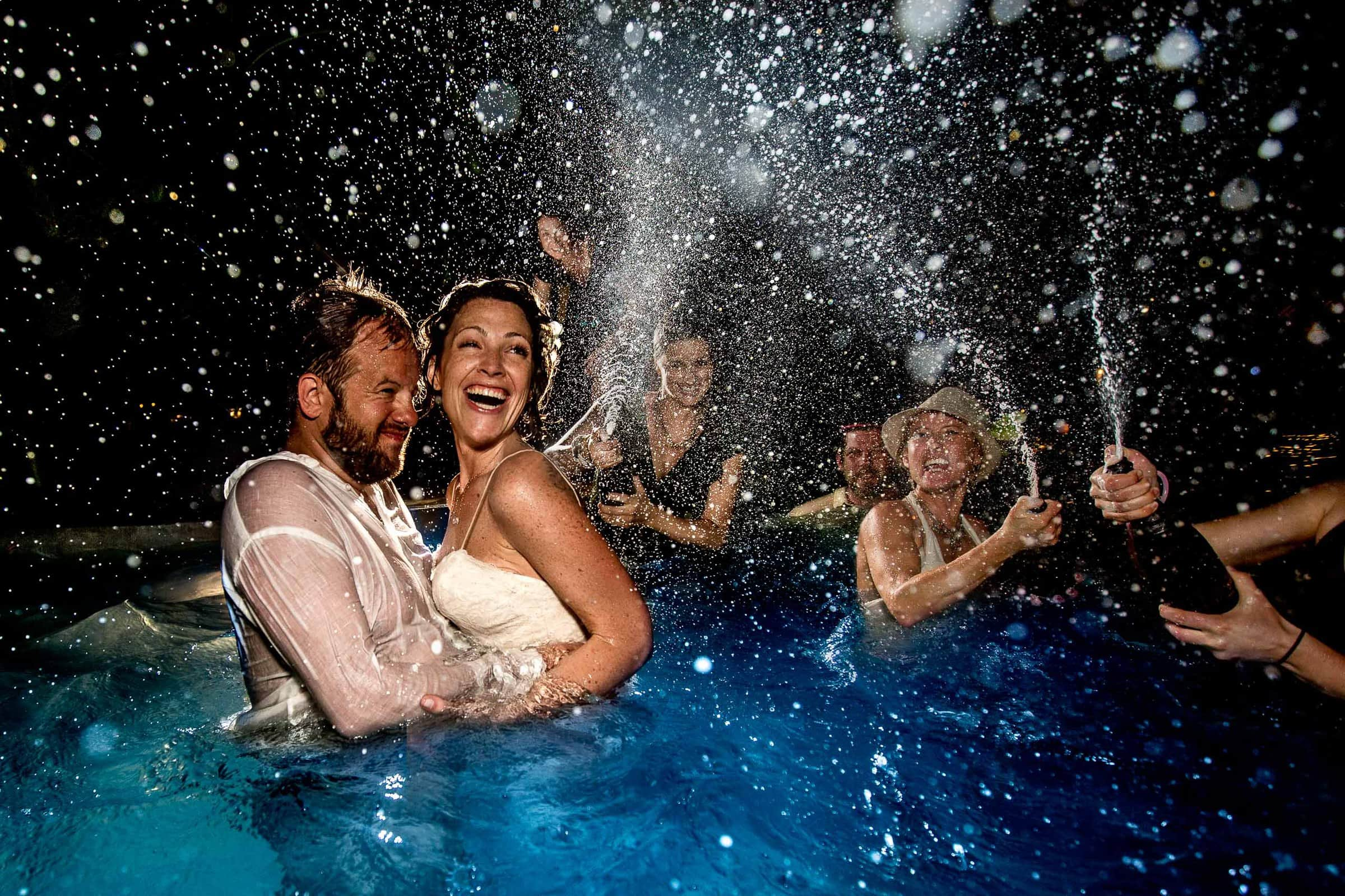 Epic pool party photo with champagne flying everywhere with friends during Nikki and Paul's Portofino Beach Resort wedding reception in Belize