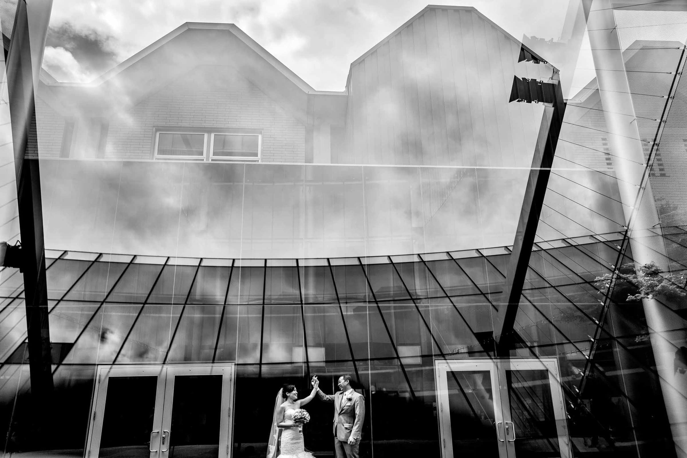 Creative portrait of a bride and groom with reflections in architecture before their Saltys wedding in Seattle, Washington.