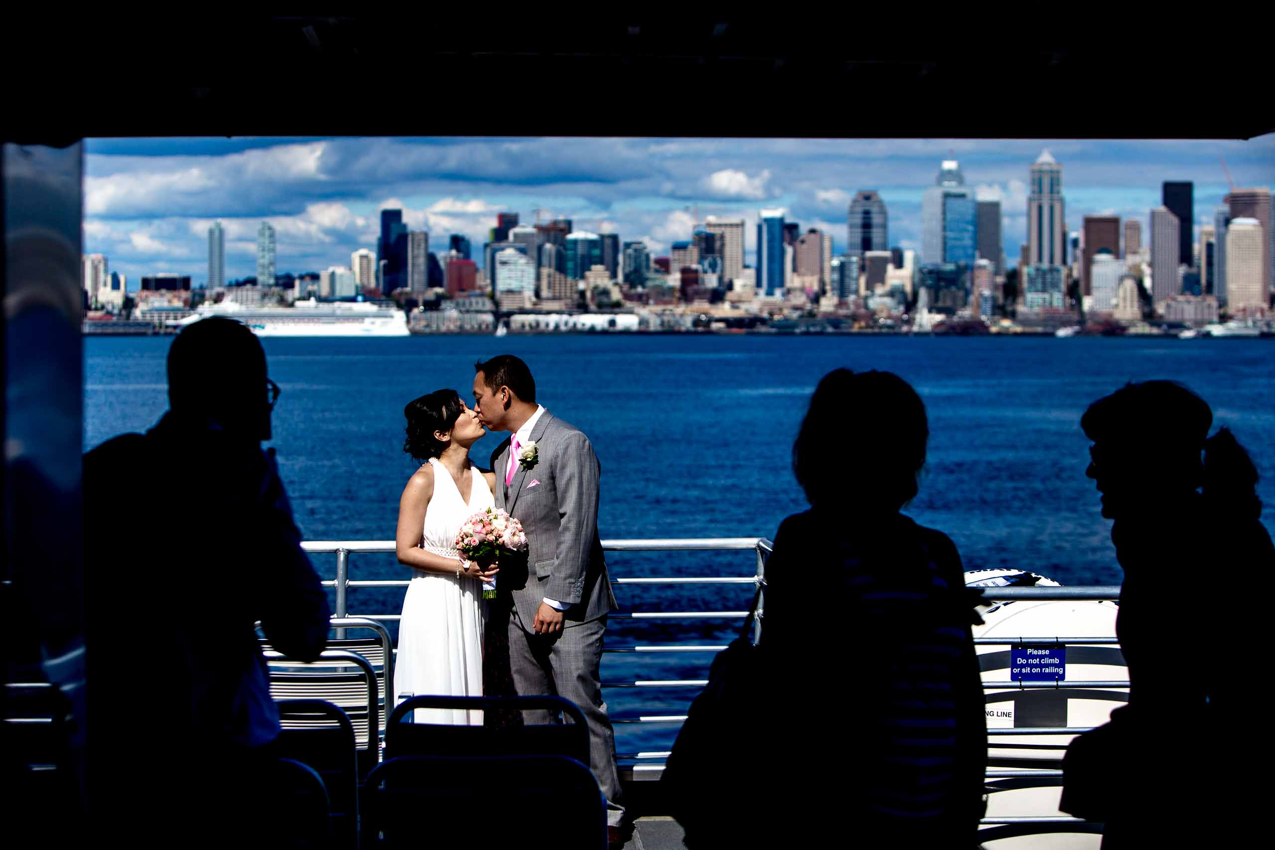 Creative photo of a bride and groom on the boat going to the Waterfront Park in Seattle before their Saltys wedding in Seattle, Washington.