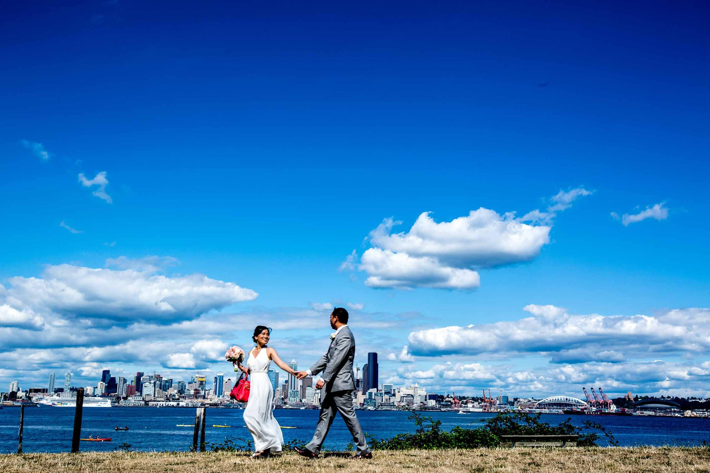 Creative photo of a bride and groom walking along the waterfront park before their Saltys wedding in Seattle, Washington.