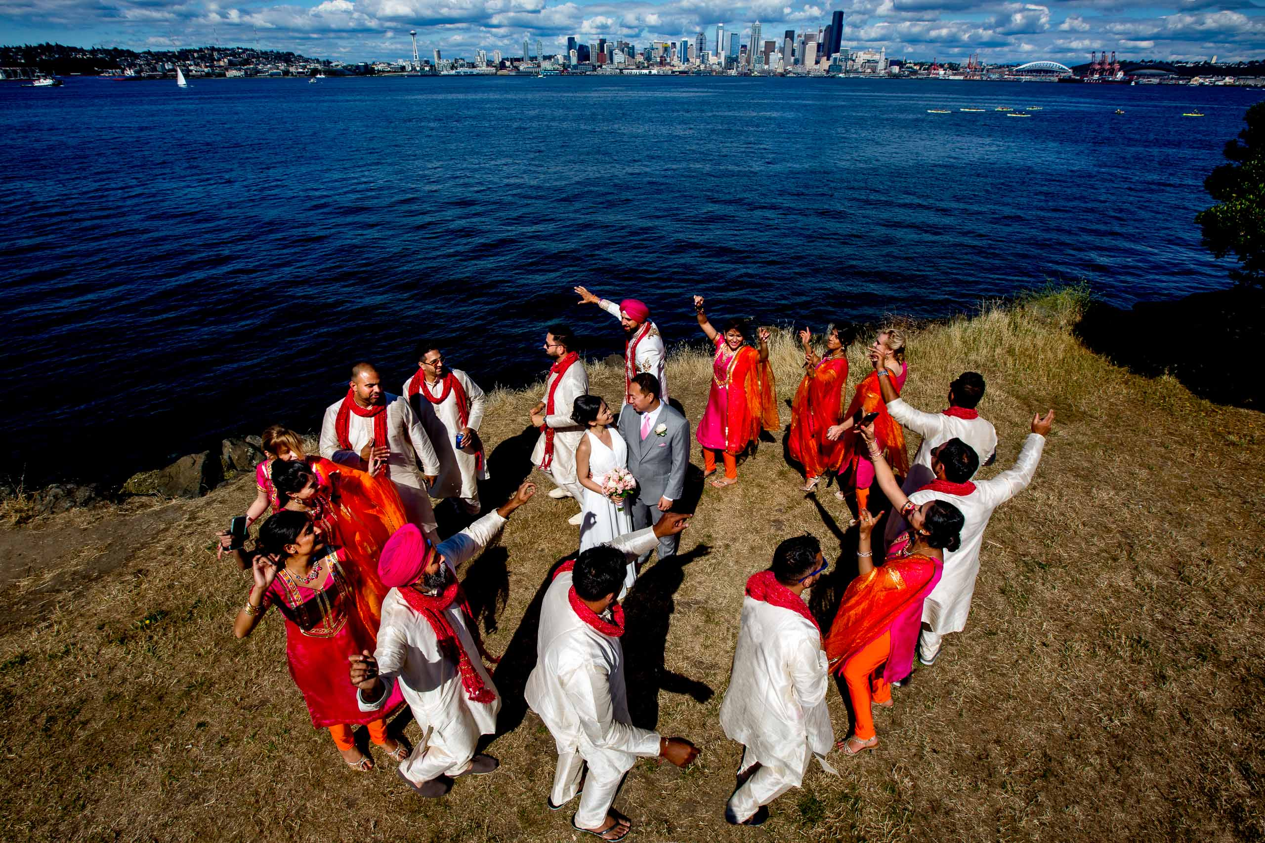 Super fun creative and colorful photo of a bride and groom being surrounded by another Indian wedding bridal party dancing on the waterfront park before their Saltys wedding in Seattle, Washington.