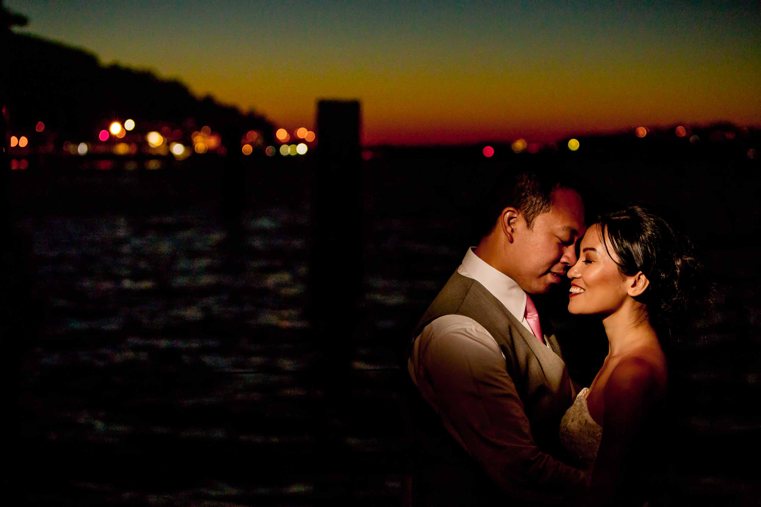 Creative portrait of a bride and groom at their Saltys wedding with Seattle's city scape in the background.