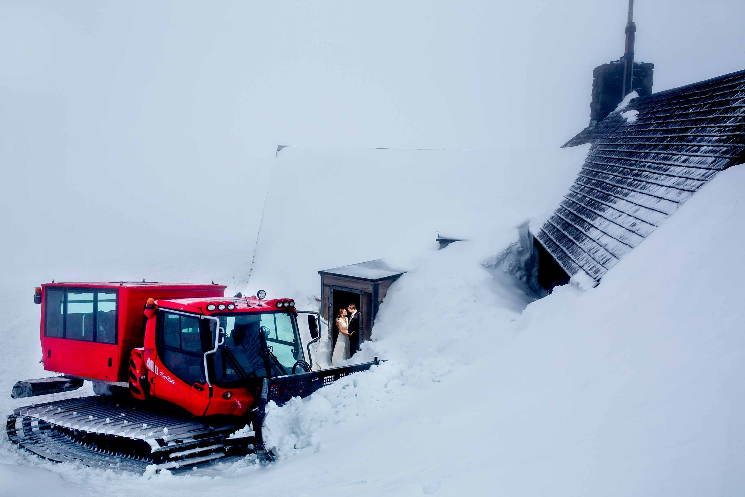 Bride and Groom in doorway leading into  Silcox Hut with big snow cat. Award winning photos by josandtree