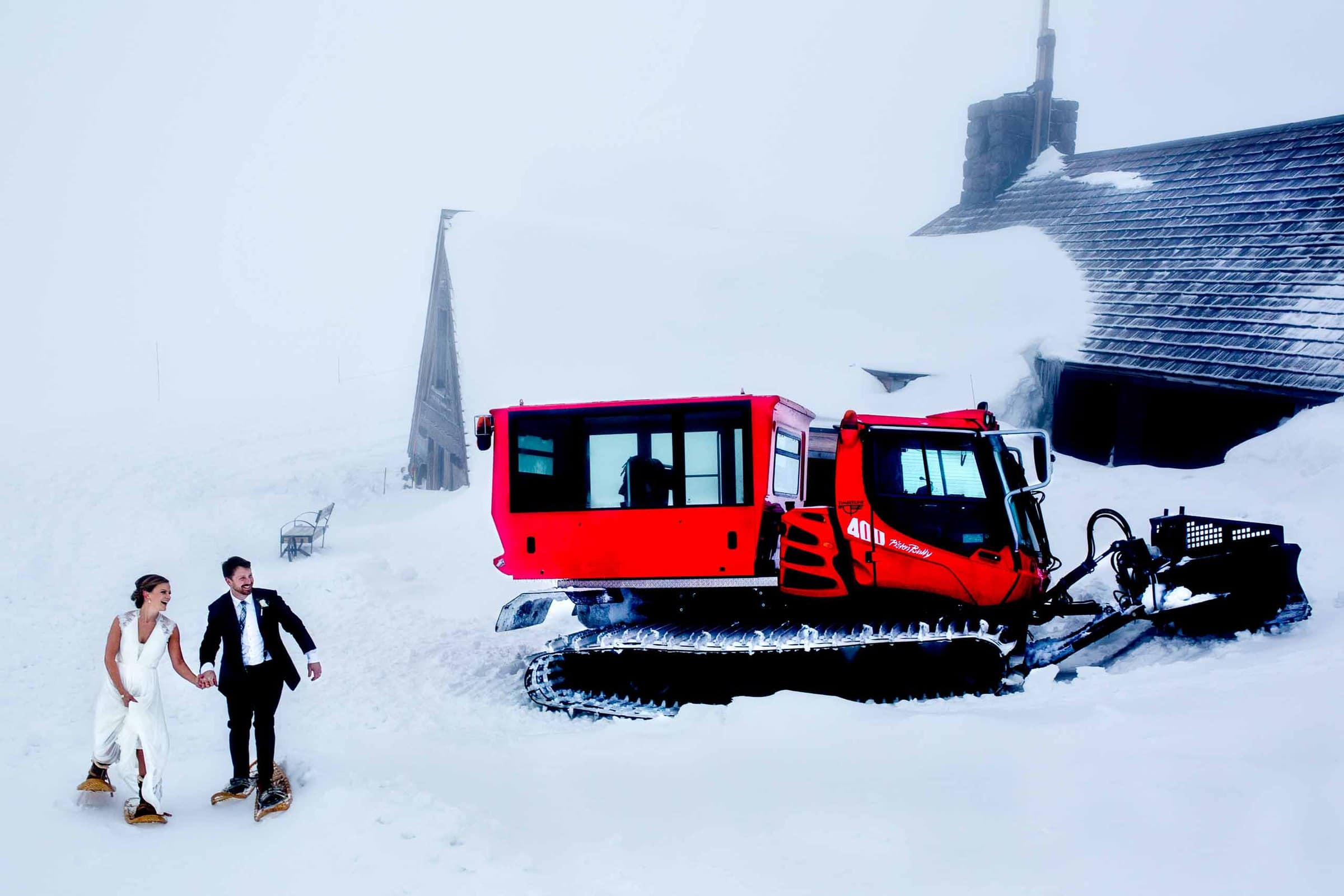 Bride and Groom walking outside big snow cat at Silcox Hut atop Mt Hood above Timberline Lodge Ski Resort.