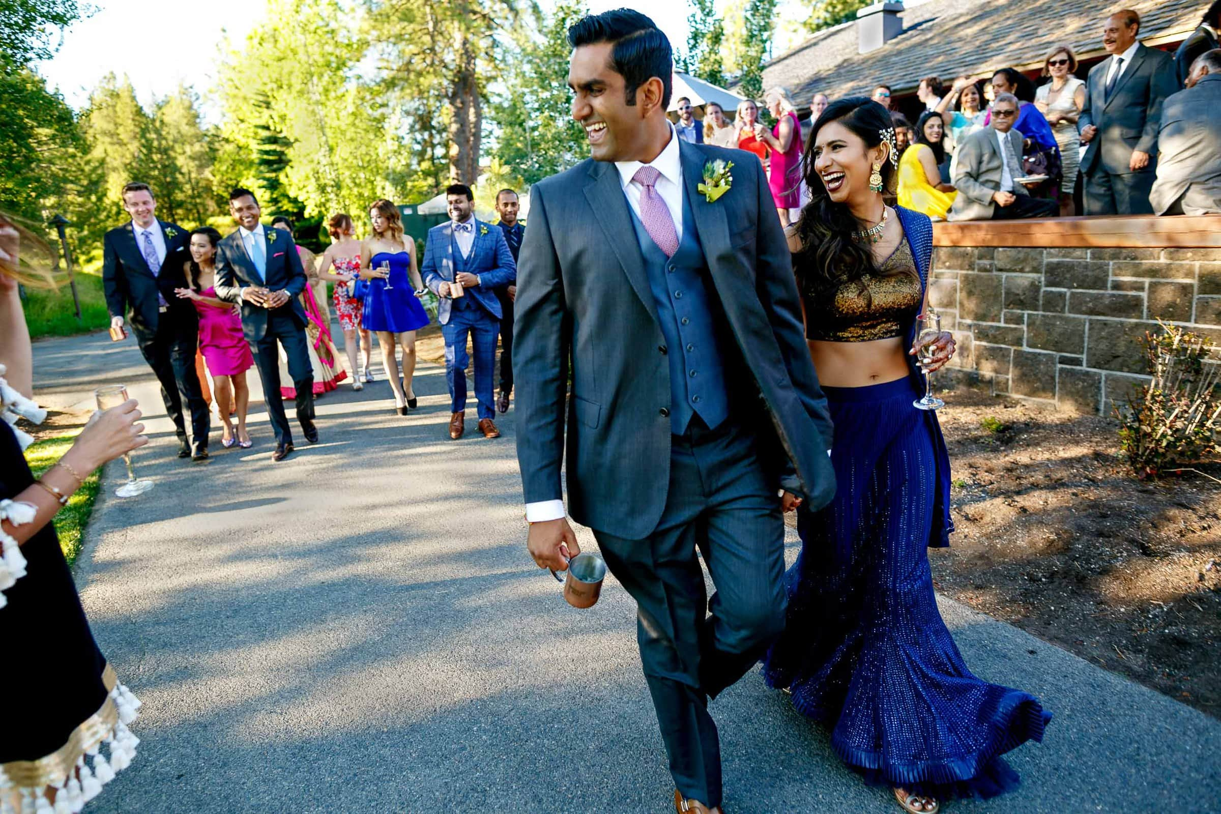 Happy photo of bride and groom entering reception during an Indian Sunriver Resort wedding in Bend Oregon in Central Oregon.