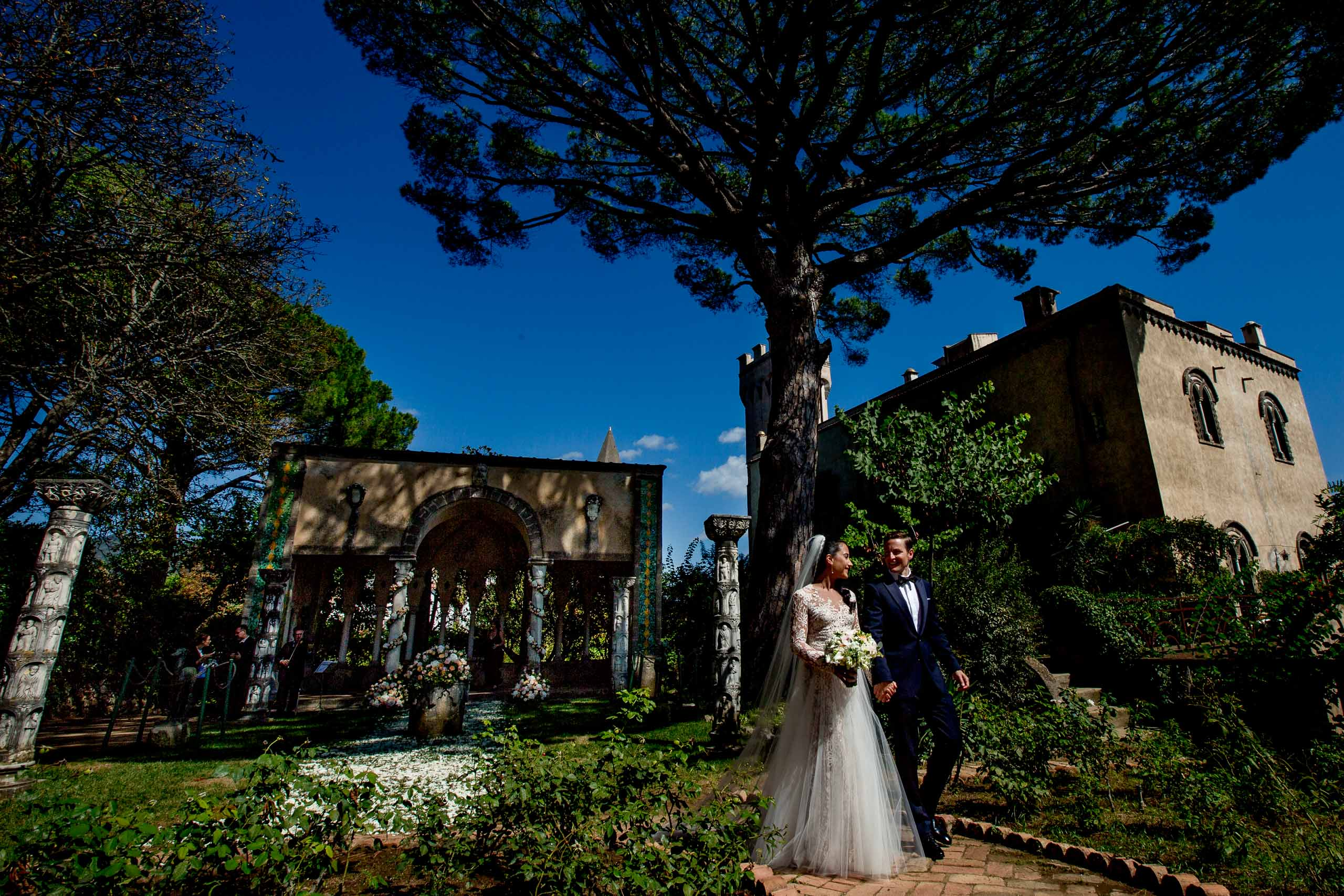 Gorgeous bride and groom walking through Villa Cimbrone garden just after their ceremony for their Ravello elopement along the Amafi Coast in Italy