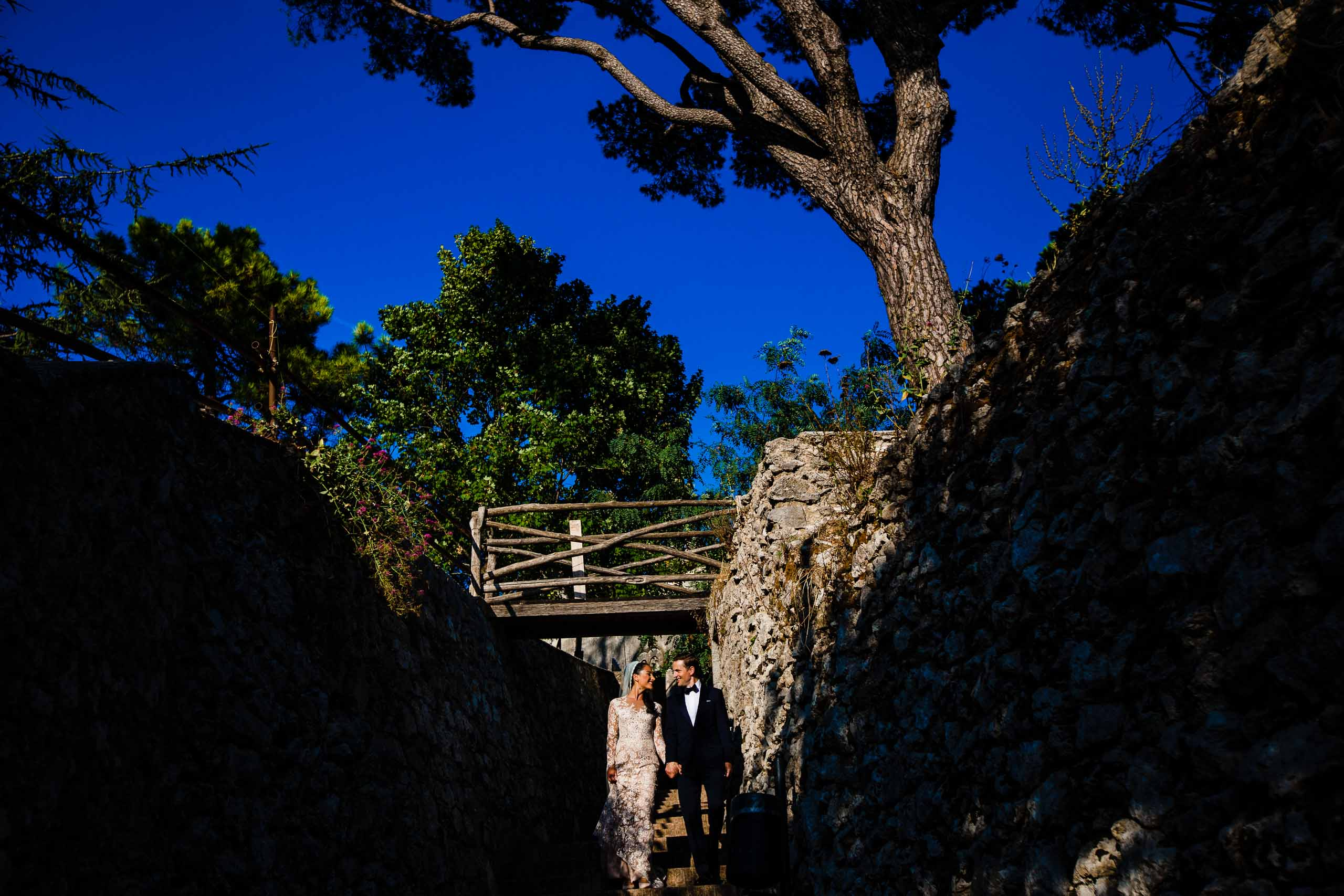 Gorgeous light on a bride and groom walking through Villa Cimbrone back streets during their Ravello elopement in Amalfi, Italy