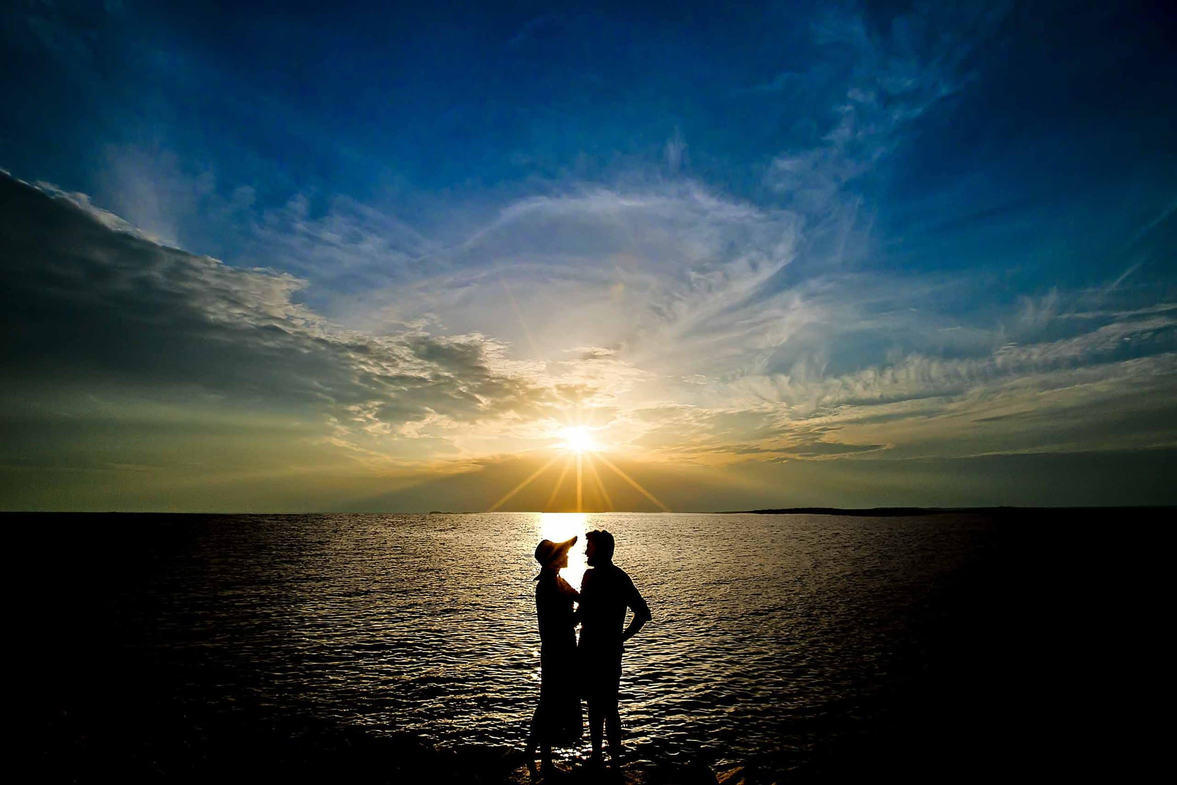 Beautiful silhouettes of lisa and brian with friends at sunset before their Chesapeake Bay wedding in Maryland at Wades Point Inn.