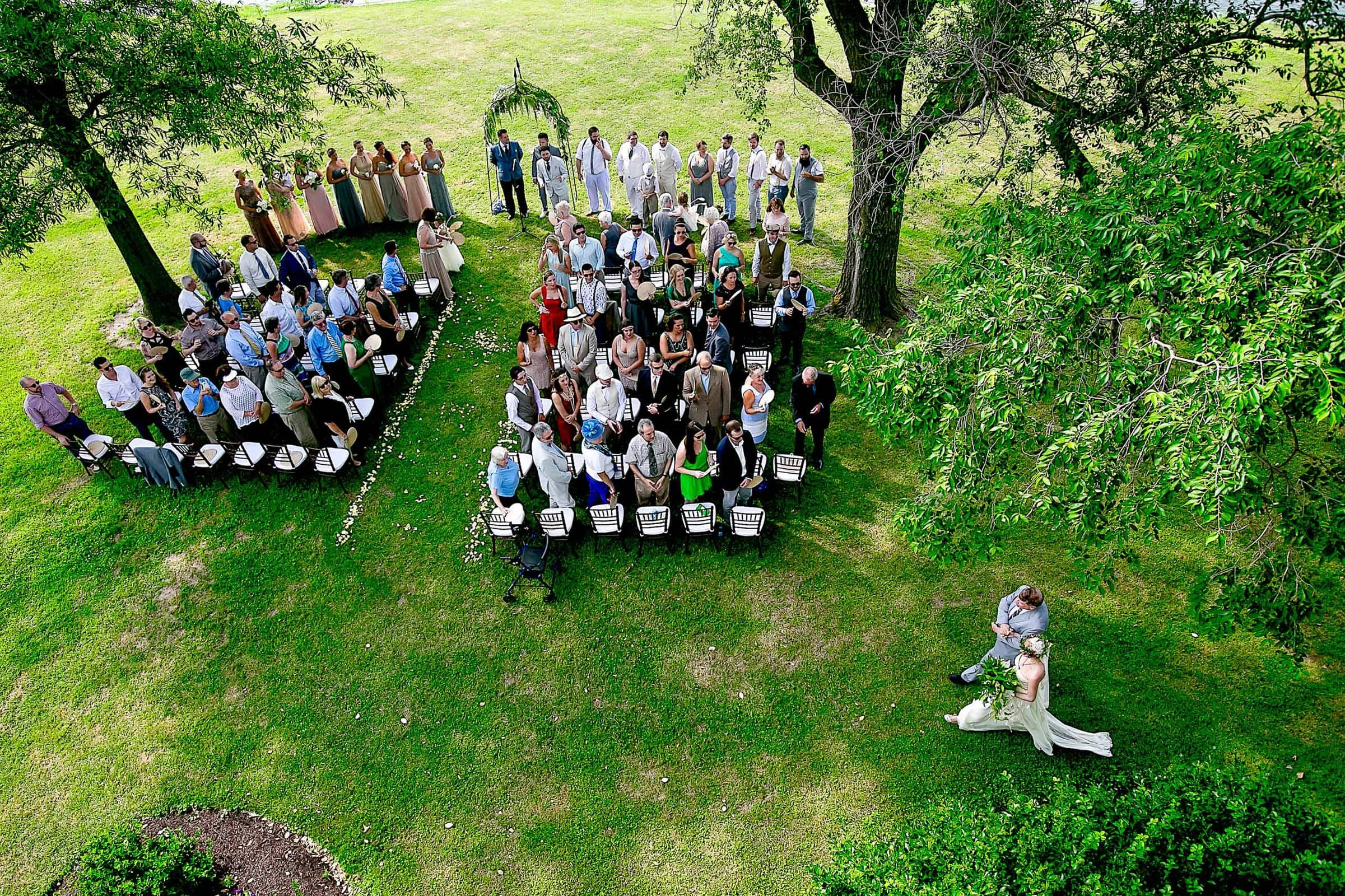 Wide angle perspective of bride walking into ceremony during a Chesapeake Bay wedding in Maryland at Wades Point Inn.