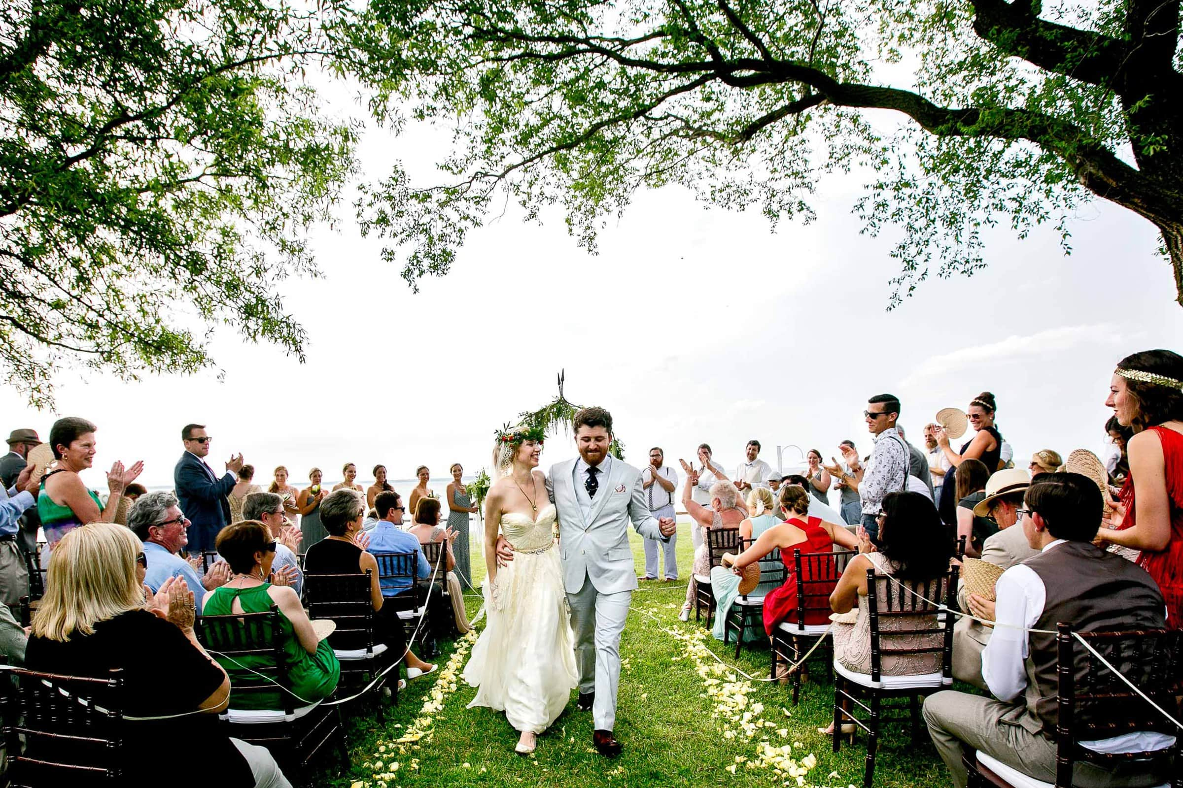 Bride and groom exiting a gorgeous Chesapeake Bay wedding ceremony in Maryland at Wades Point Inn.