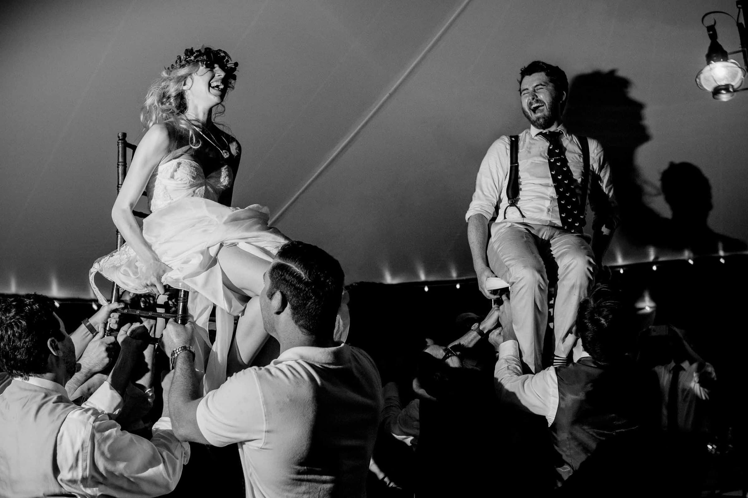 Bride and groom in a wild hora dance on chairs during their Chesapeake Bay wedding ceremony in Maryland at Wades Point Inn.