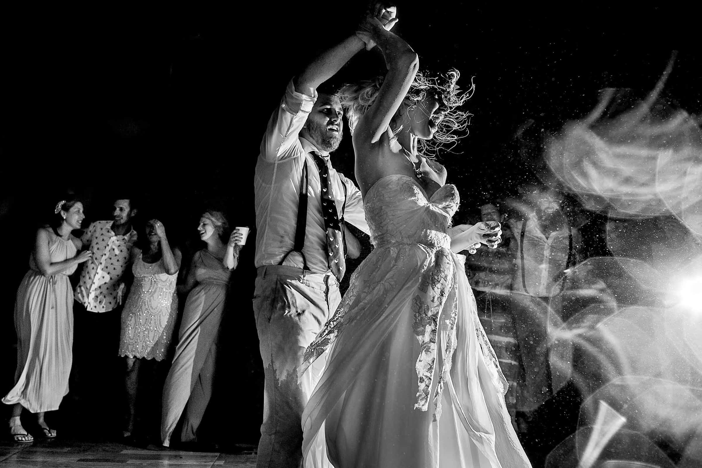 Bride and groom dancing wild in a rain storm during their Chesapeake Bay wedding ceremony in Maryland at Wades Point Inn.