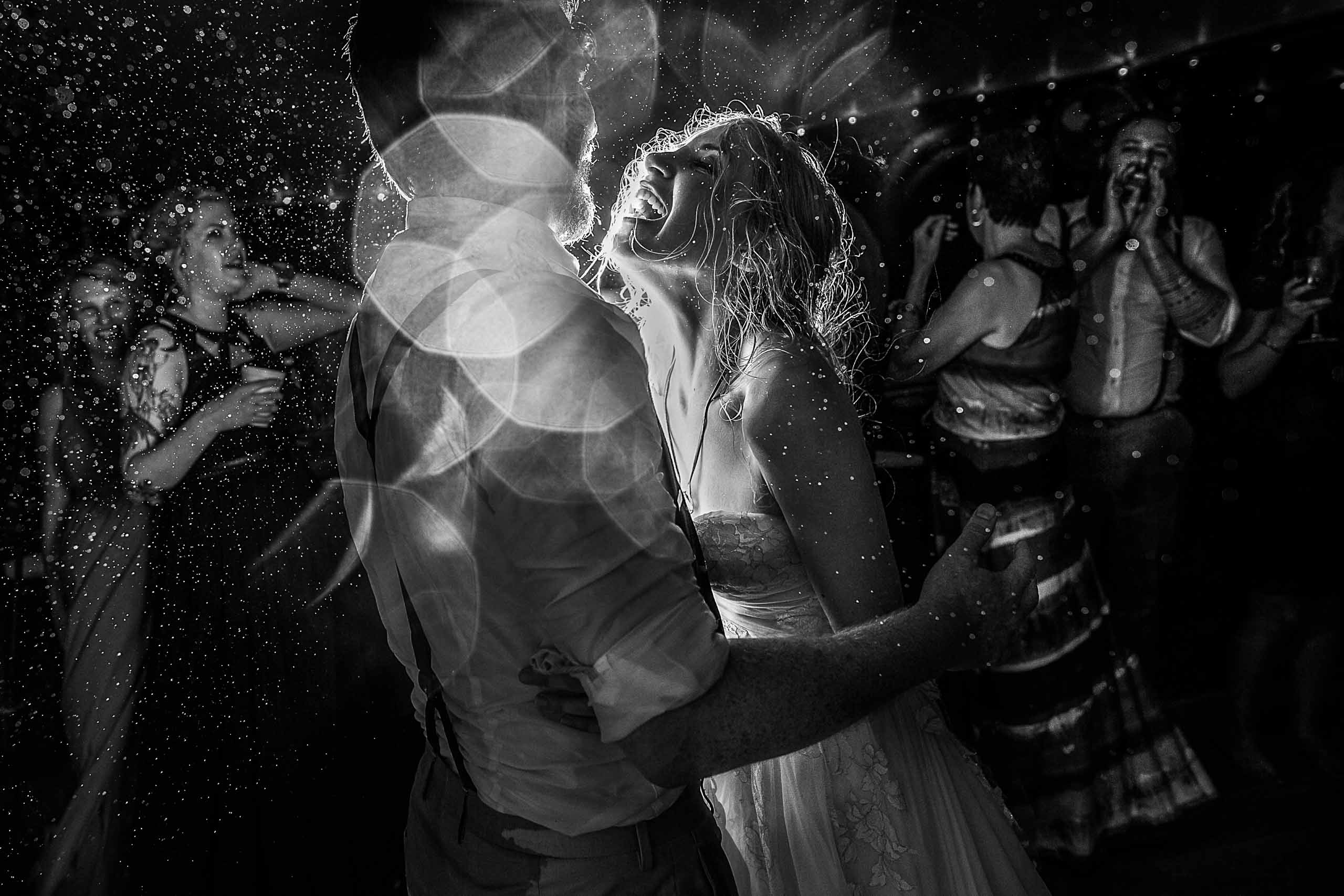 Fearless Photographers award winning photo of a Bride and groom dancing wild in a rain storm during their Chesapeake Bay wedding ceremony in Maryland at Wades Point Inn.