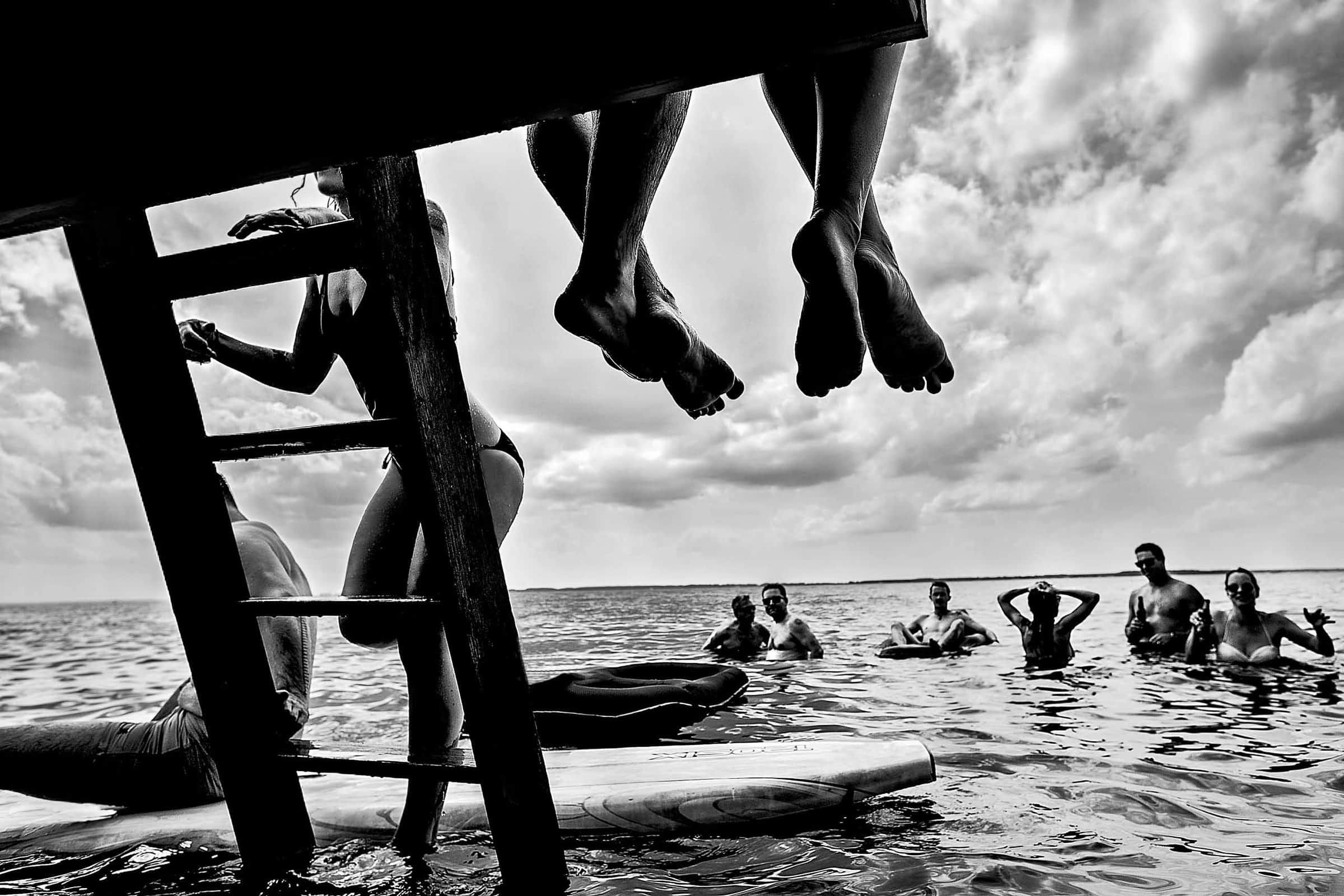 Fearless Photographers award winning photo of a Bride and groom resting their feet over a dock with friends swimming at their Chesapeake Bay wedding ceremony in Maryland at Wades Point Inn.