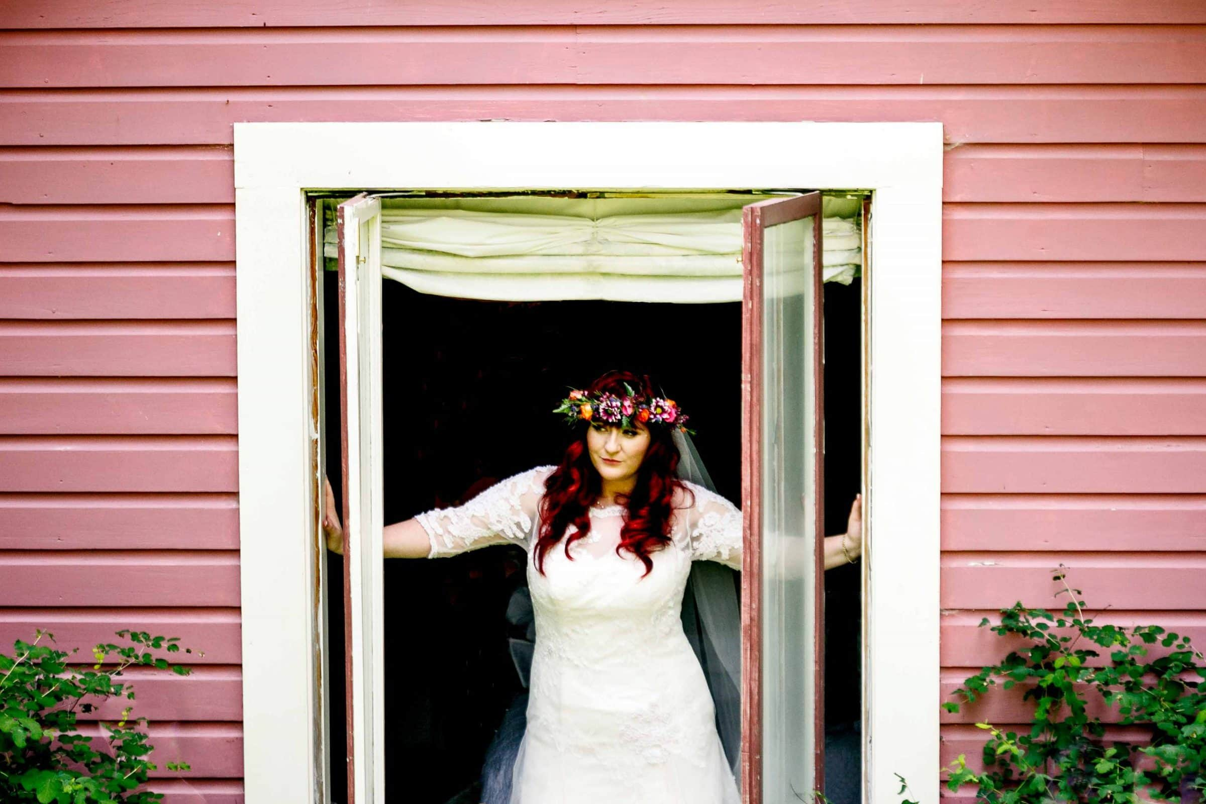 A colorful bride leaning through a window before her Mt Hood Organic Farms Wedding ceremony in the orchard house.