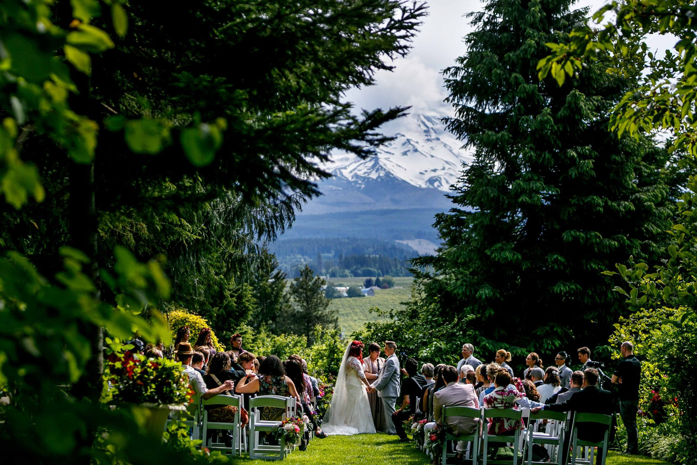 A wide angle perspective of a same sex wedding ceremony at the Mt Hood Organic Farms wedding with Mt Hood in the backdrop