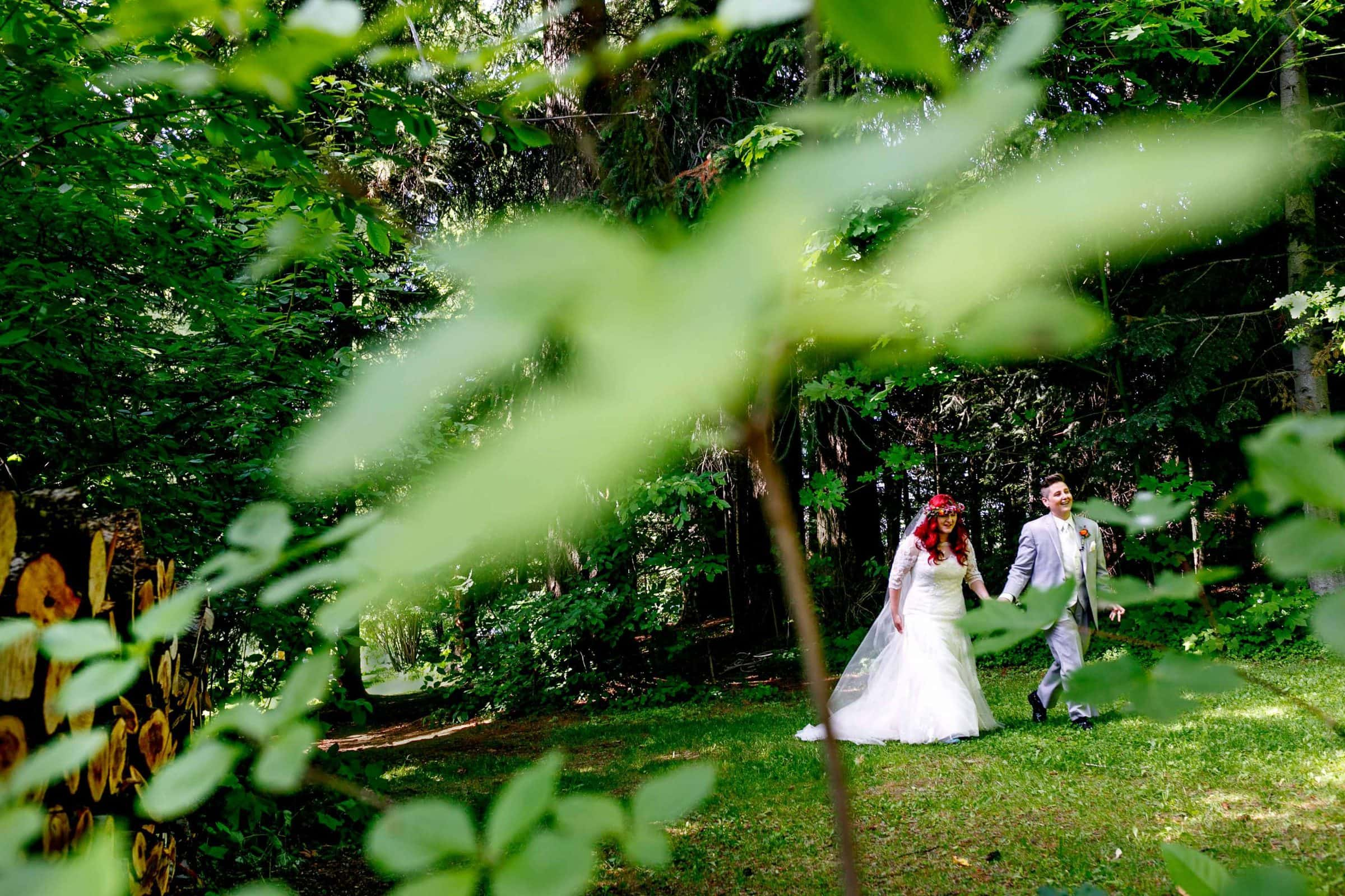 A fun wedding photo of a bride and a bride walking through the forest after their Mt Hood Organic Farms wedding ceremony