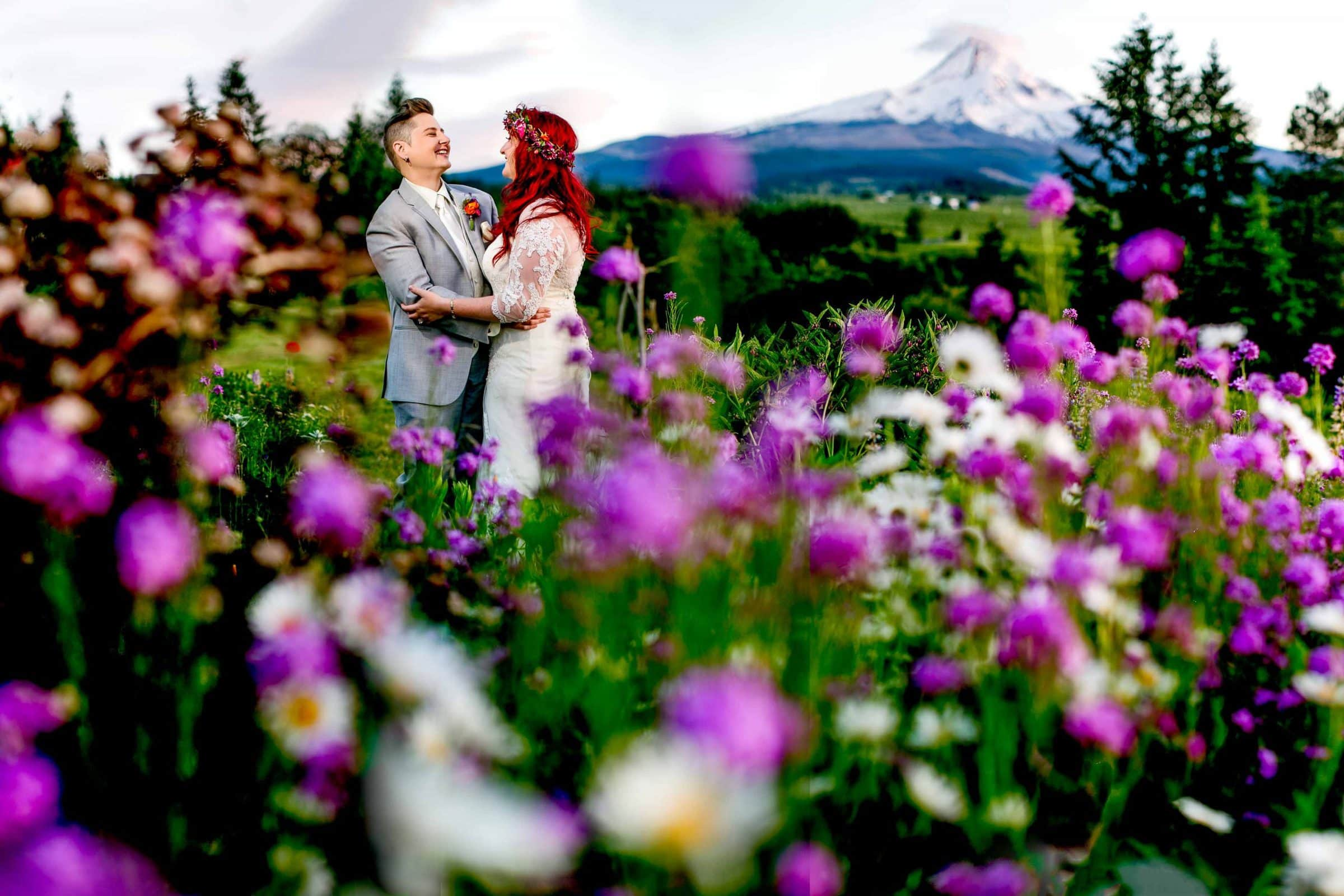 A bride and bride embracing in the colorful flower field during a Mt Hood Organic Farms wedding reception