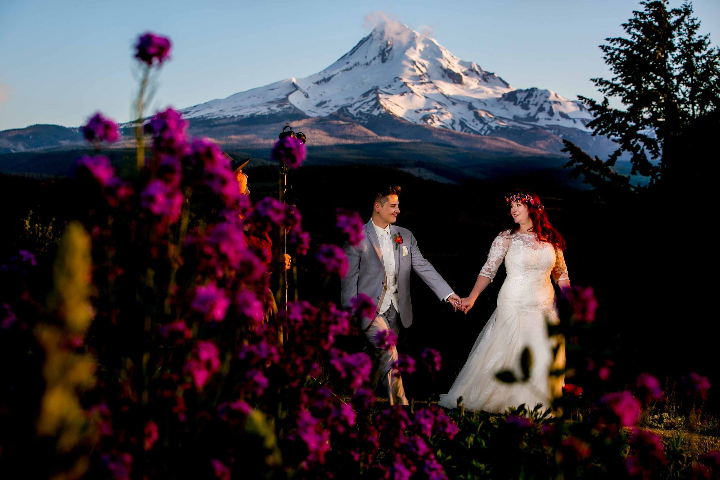 A bride and bride walking in the colorful flower field during a Mt Hood Organic Farms wedding at sunset