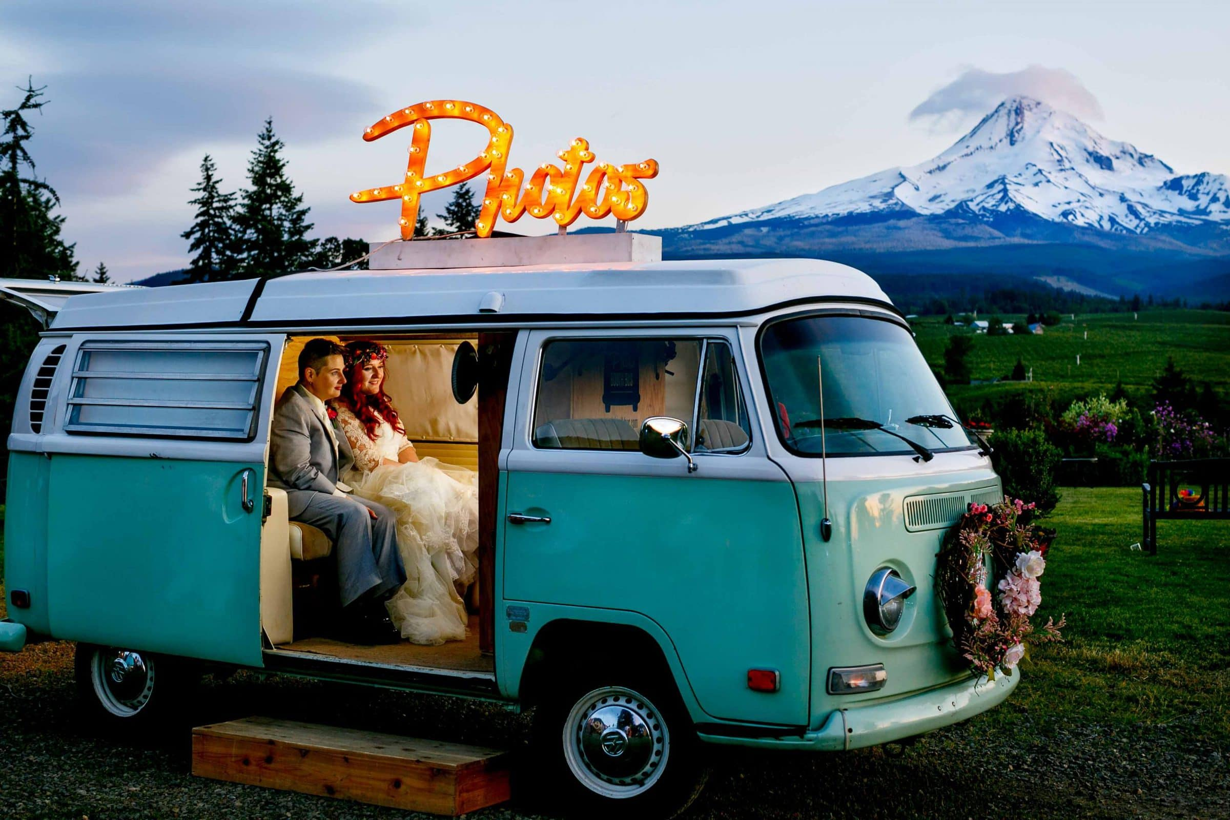 A bride and bride in a VW bus photo booth during their Mt Hood Organic Farms wedding reception at sunset