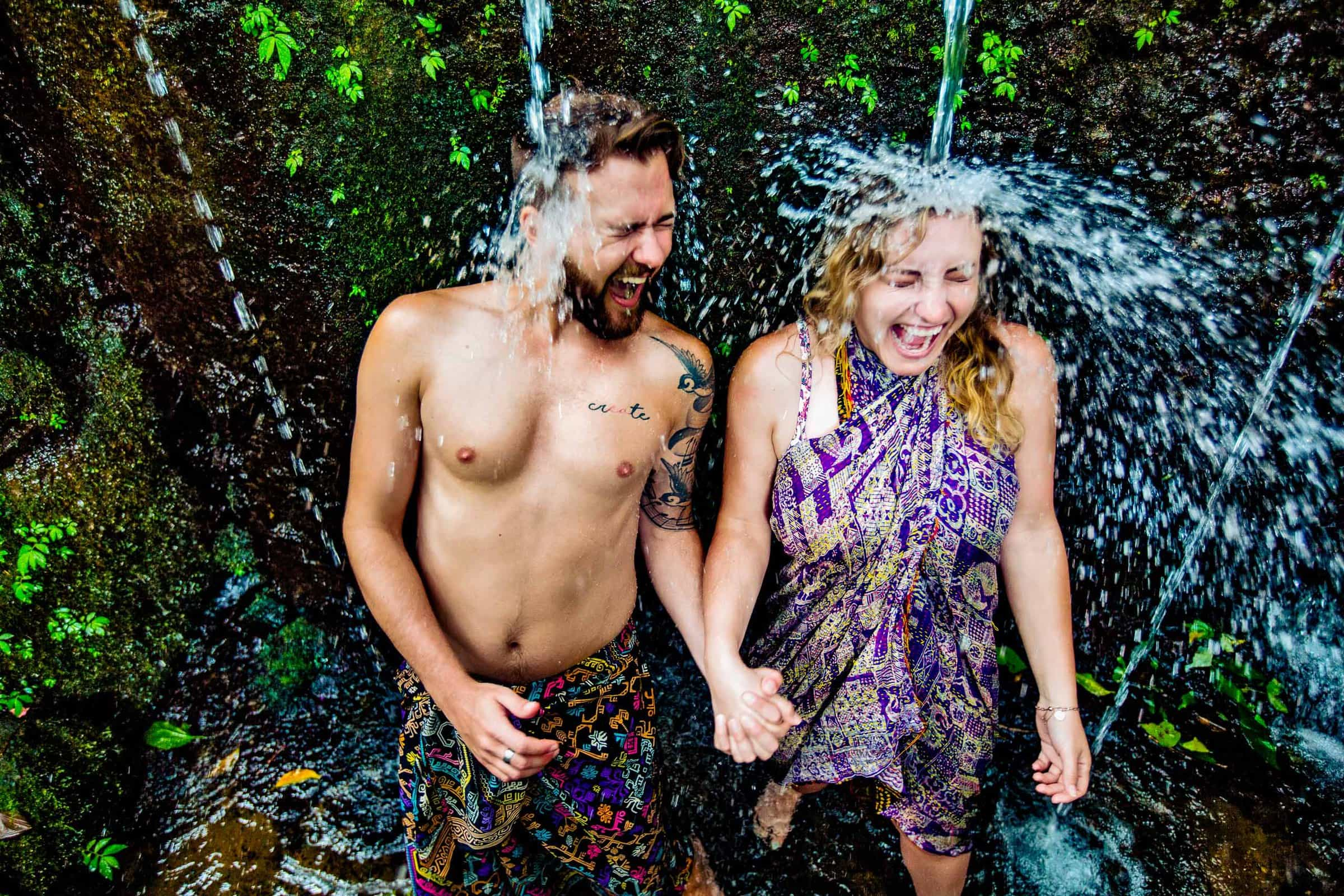 Bali engagement photo of a couple under a waterfall laughing