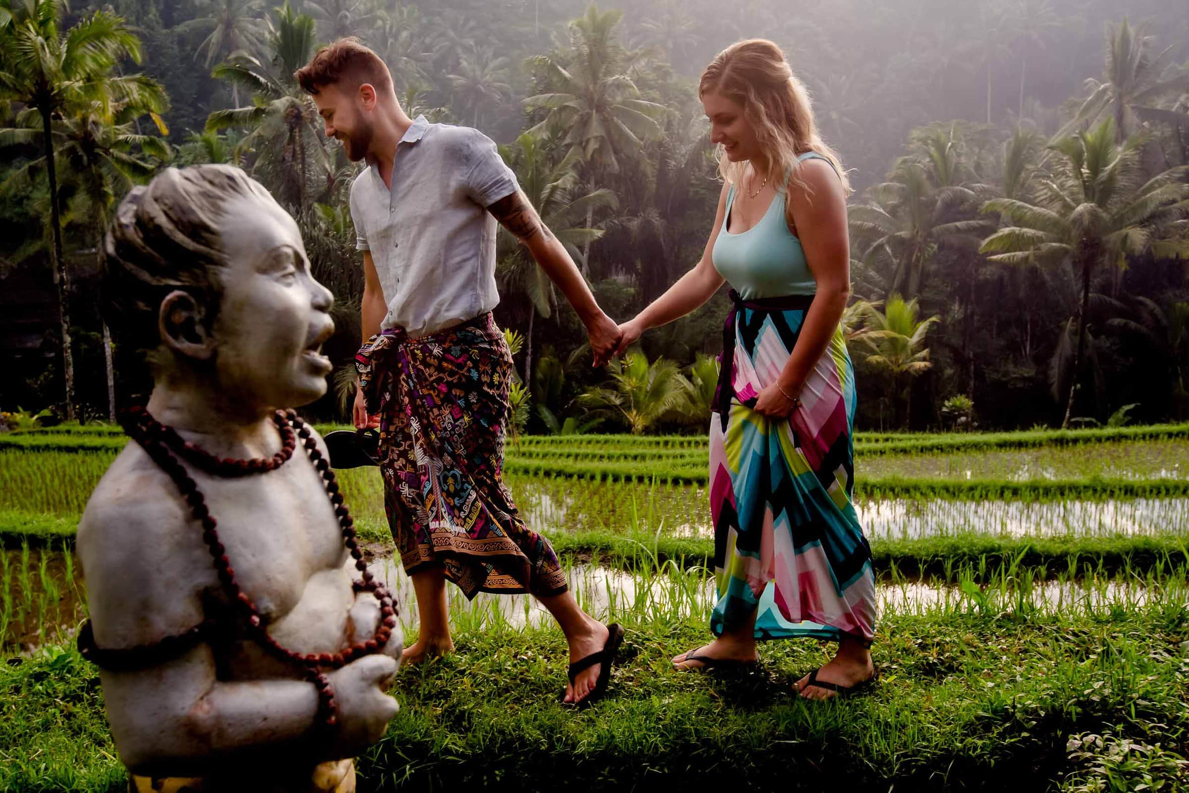 Early morning Bali engagement photo of a couple walking through rice fields