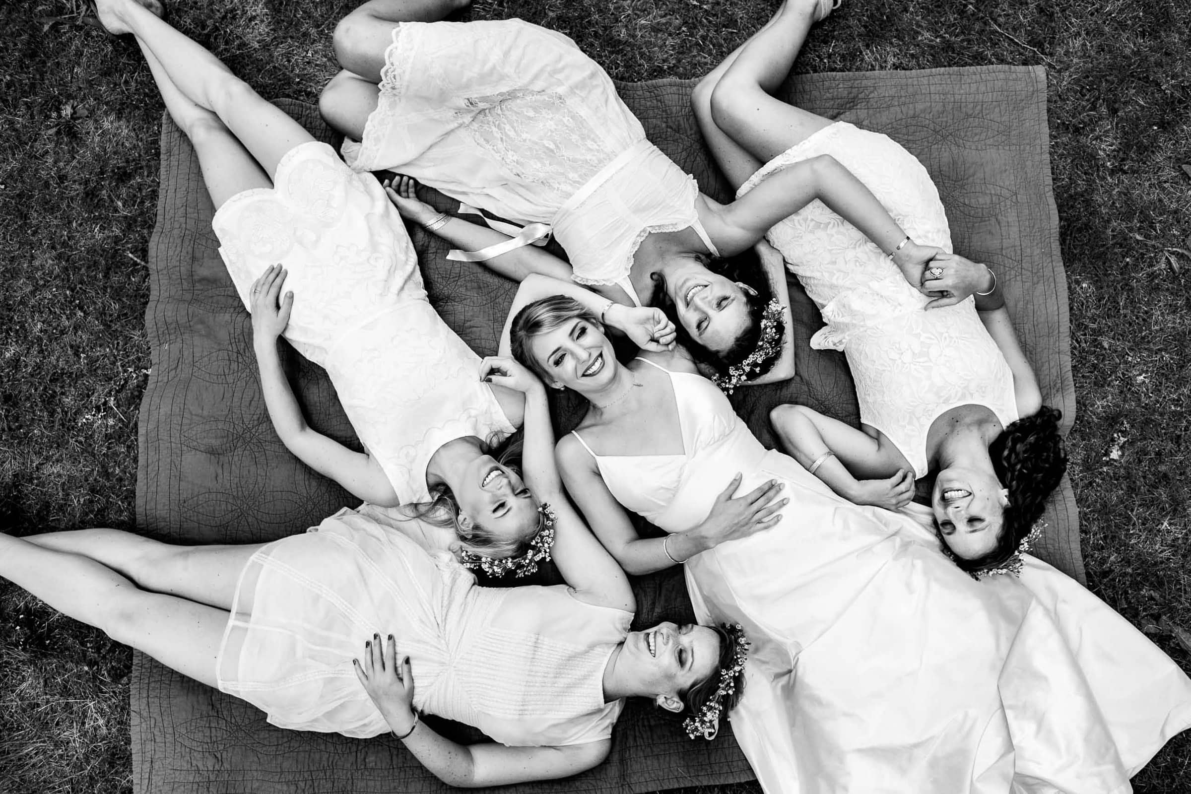 A drone photo of a bride with her best friends all laying together before heading out to their camp angleos wedding