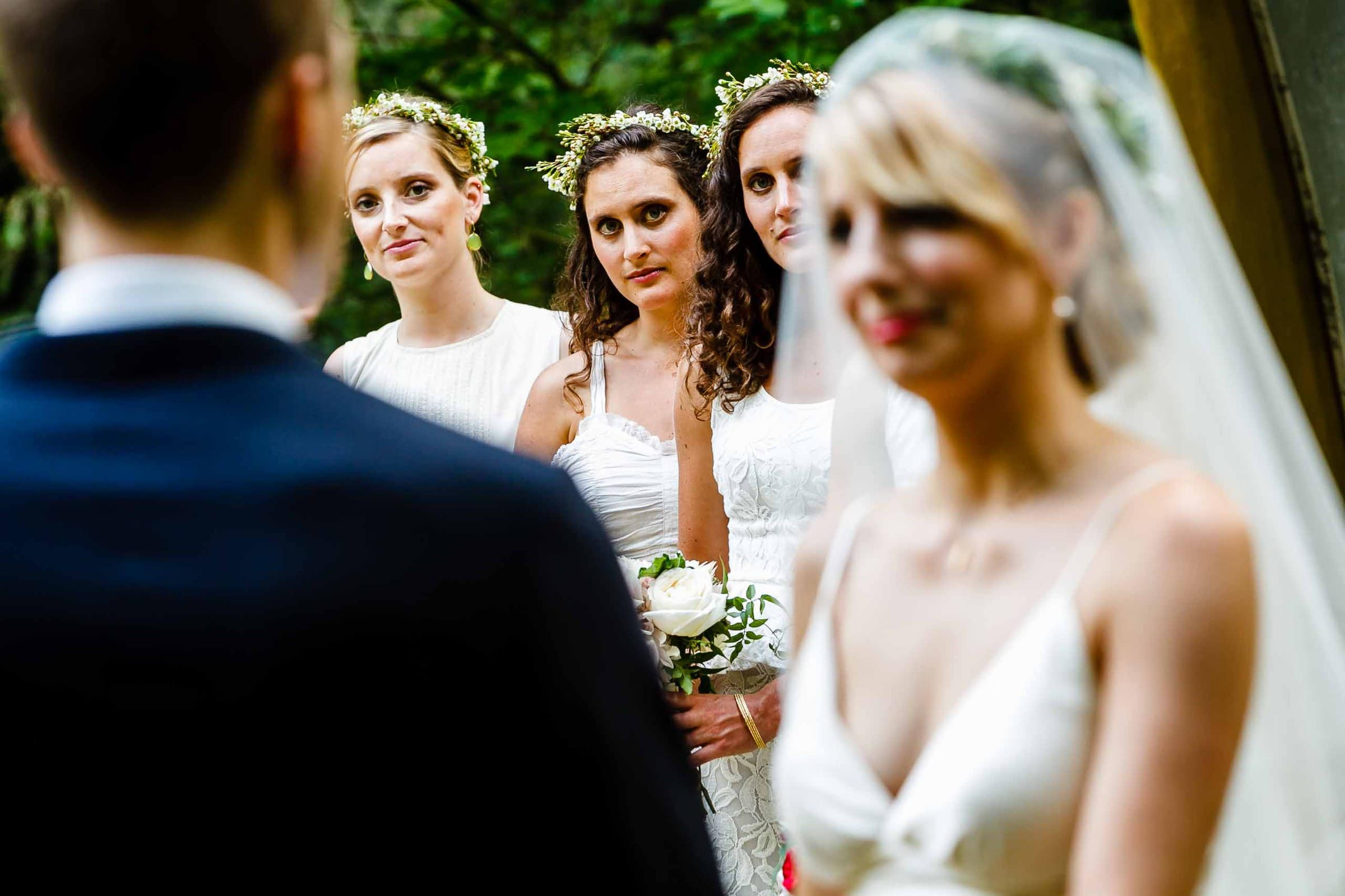 A photo with storytelling depth of gorgeous bridesmaids and a bride exchanging vows during a camp angleos wedding ceremony in Oregon