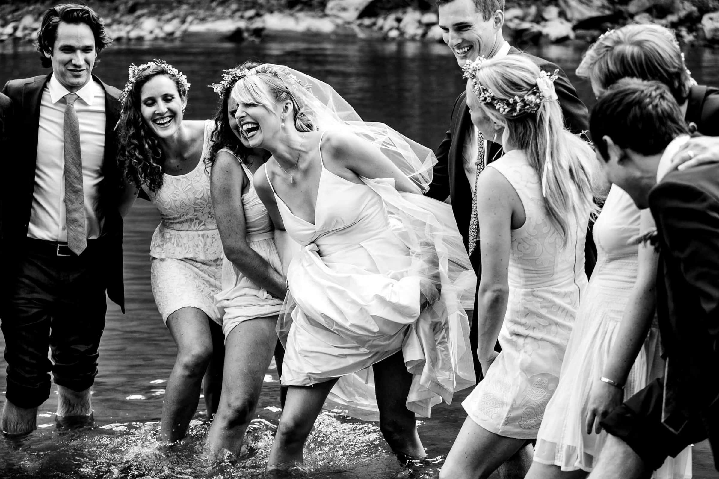 Award winning wedding photo of bride laughing with friends in a river in Corbett Oregon at Camp Deangelos. Photo by josandtree