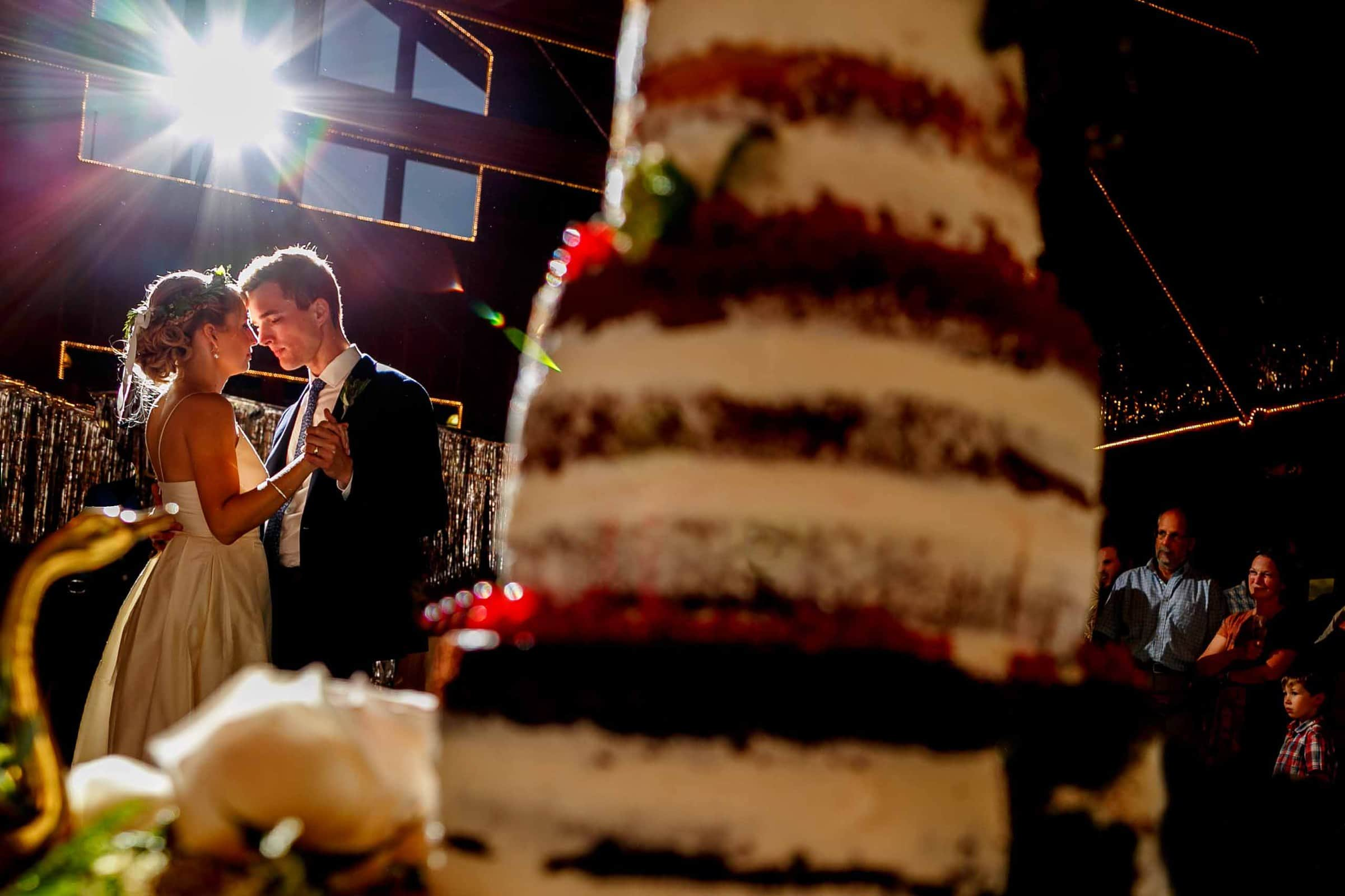A beautiful first dance photo of a bride and groom with their cake in the foreground and flare coming behind them during camp angleos wedding reception in Oregon