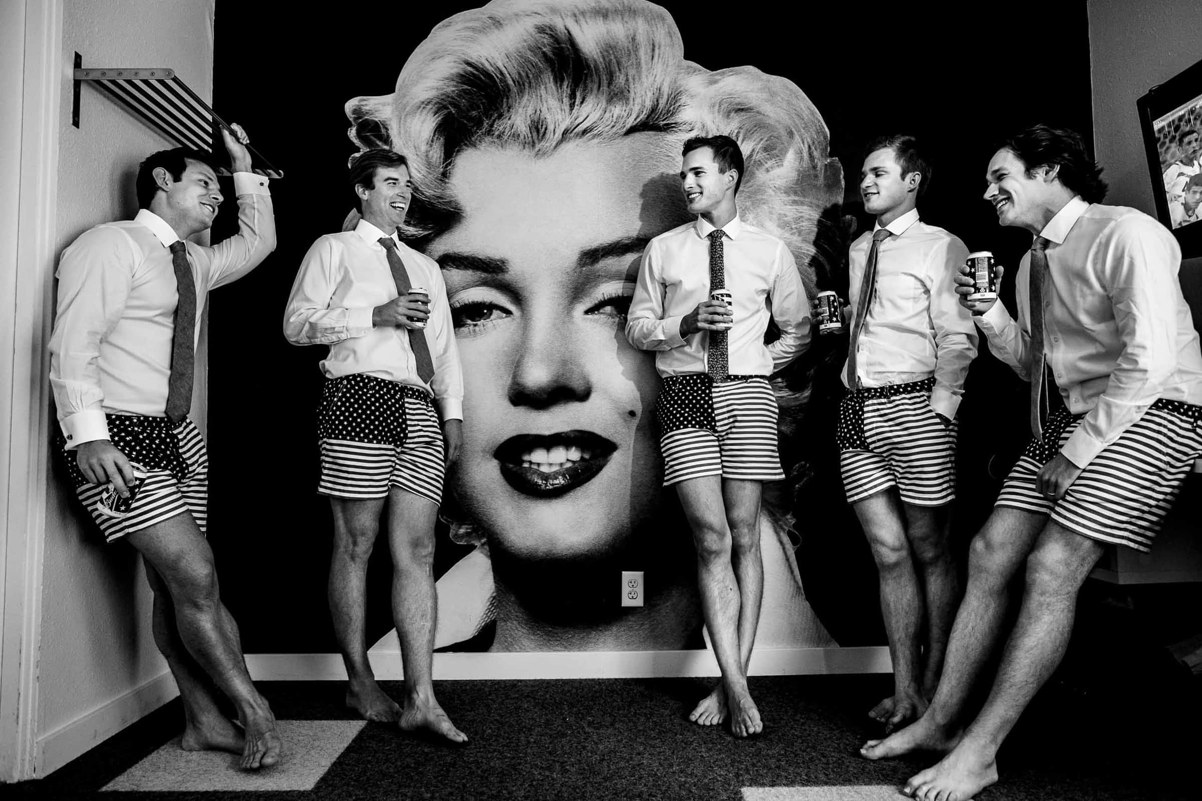 A candid black and white photo of groomsmen getting ready together with a Marylin Monroe portrait behind them before heading out to their camp angleos wedding