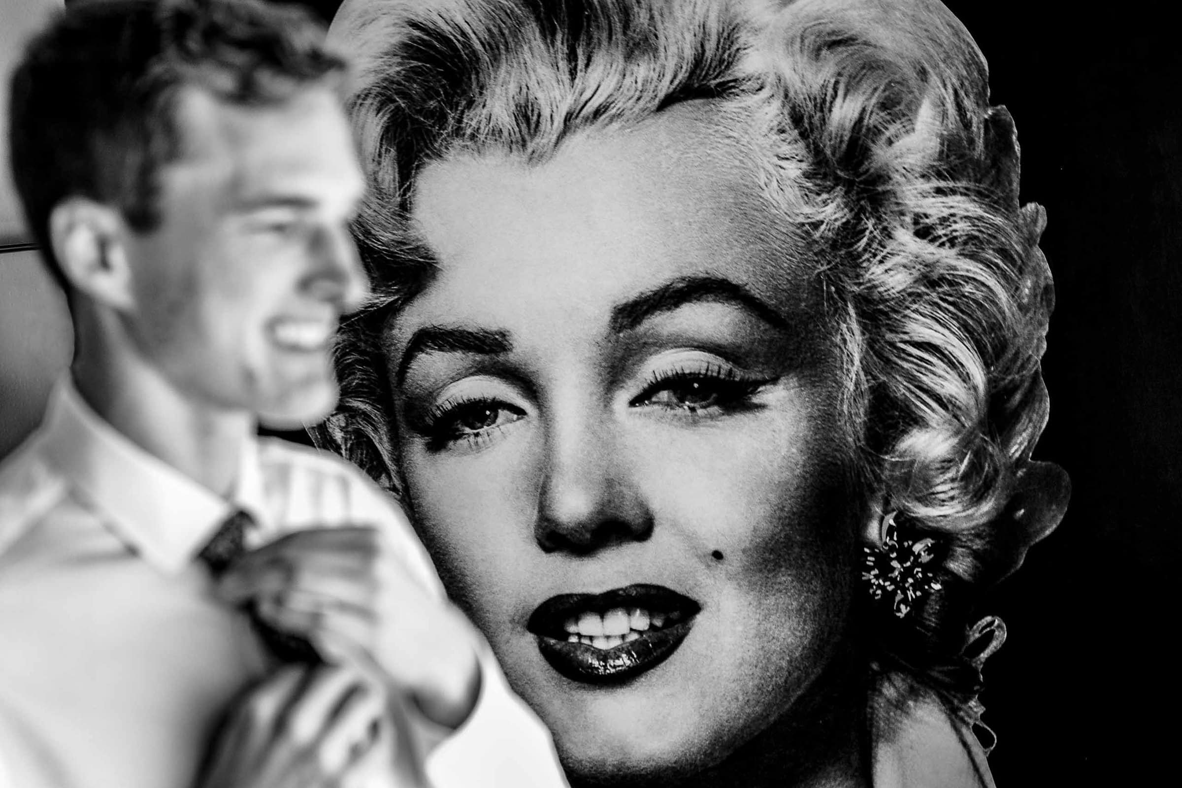 A creative photo of a groom getting ready with a massive photo of Marylin Monroe behind him before heading out to his camp angleos wedding