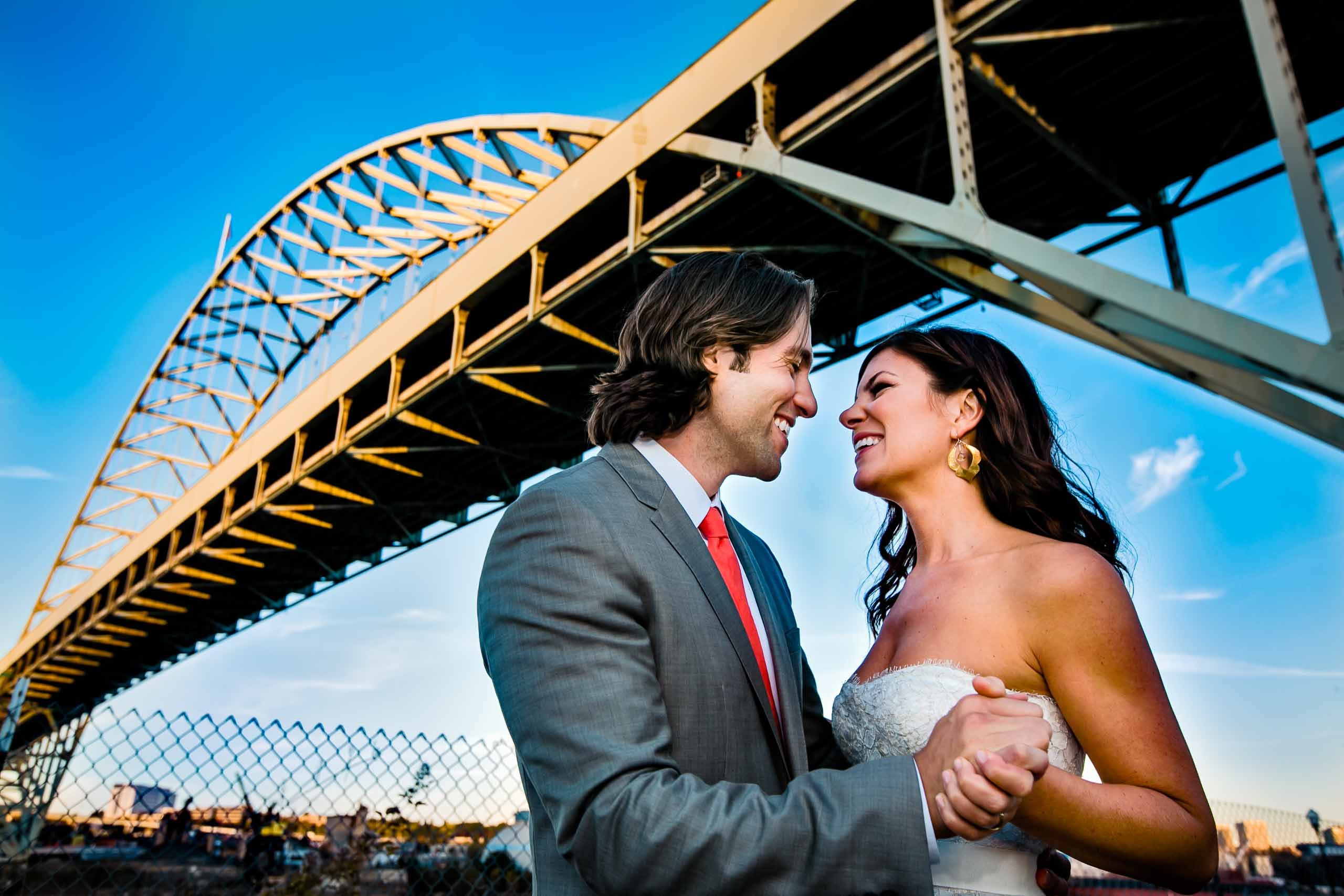 A fun and scenic photo of a bride and groom underneath the 405 bridge during their Portland wedding celebration