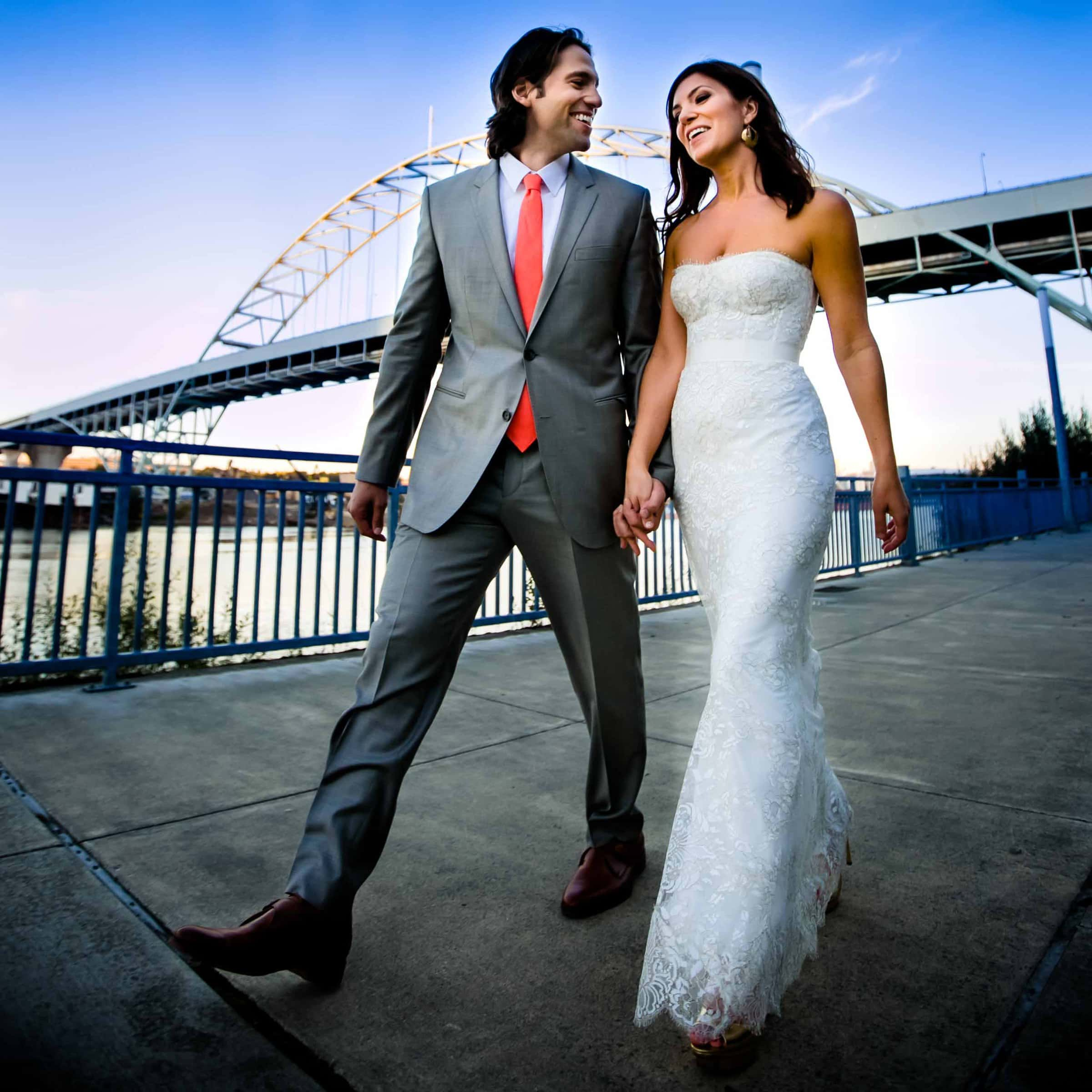 A fun and scenic photo of a bride and groom walking hand and hand underneath the 405 bridge during their Portland wedding celebration