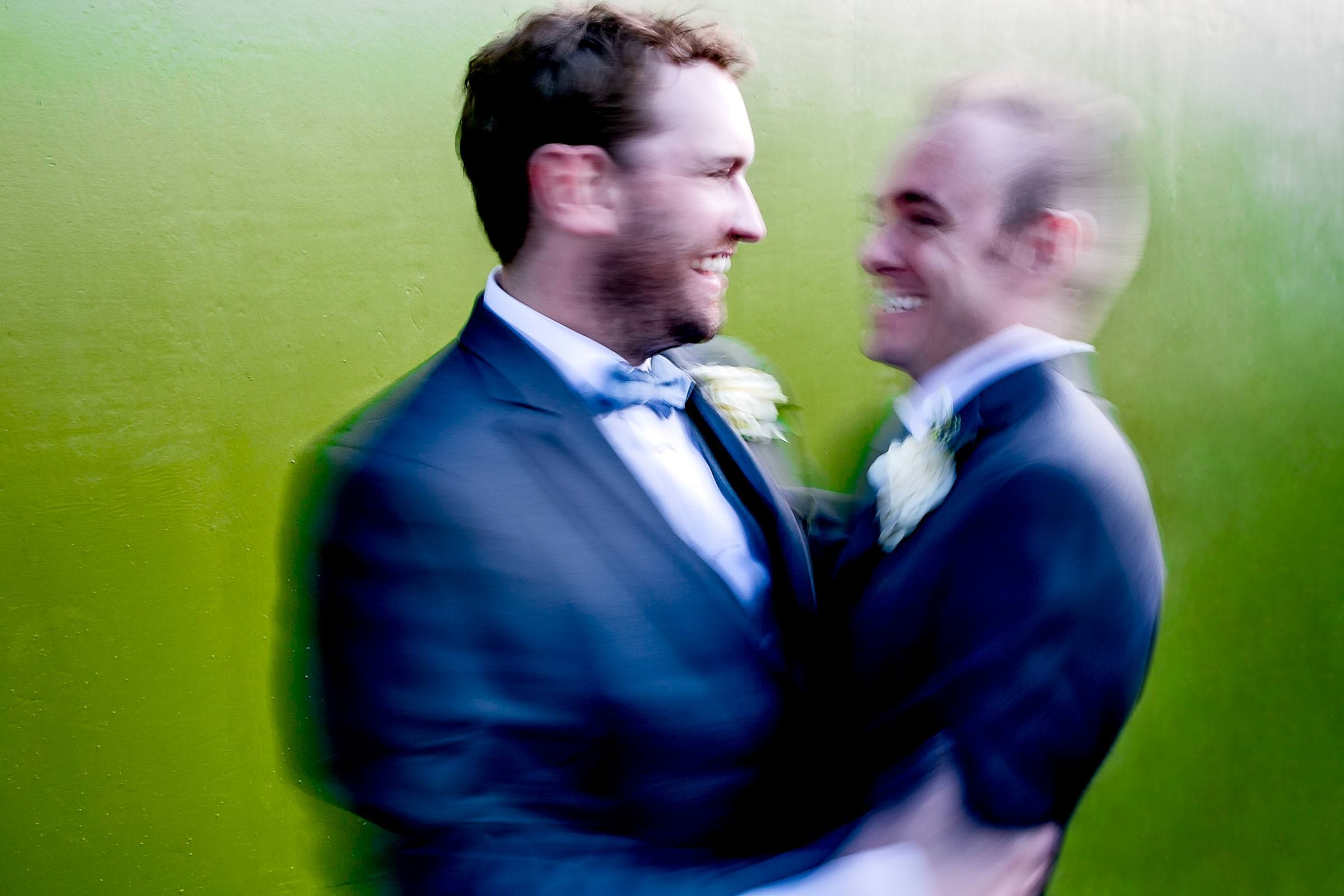 Two grooms spinning in a hug just after their Portland Castaway wedding