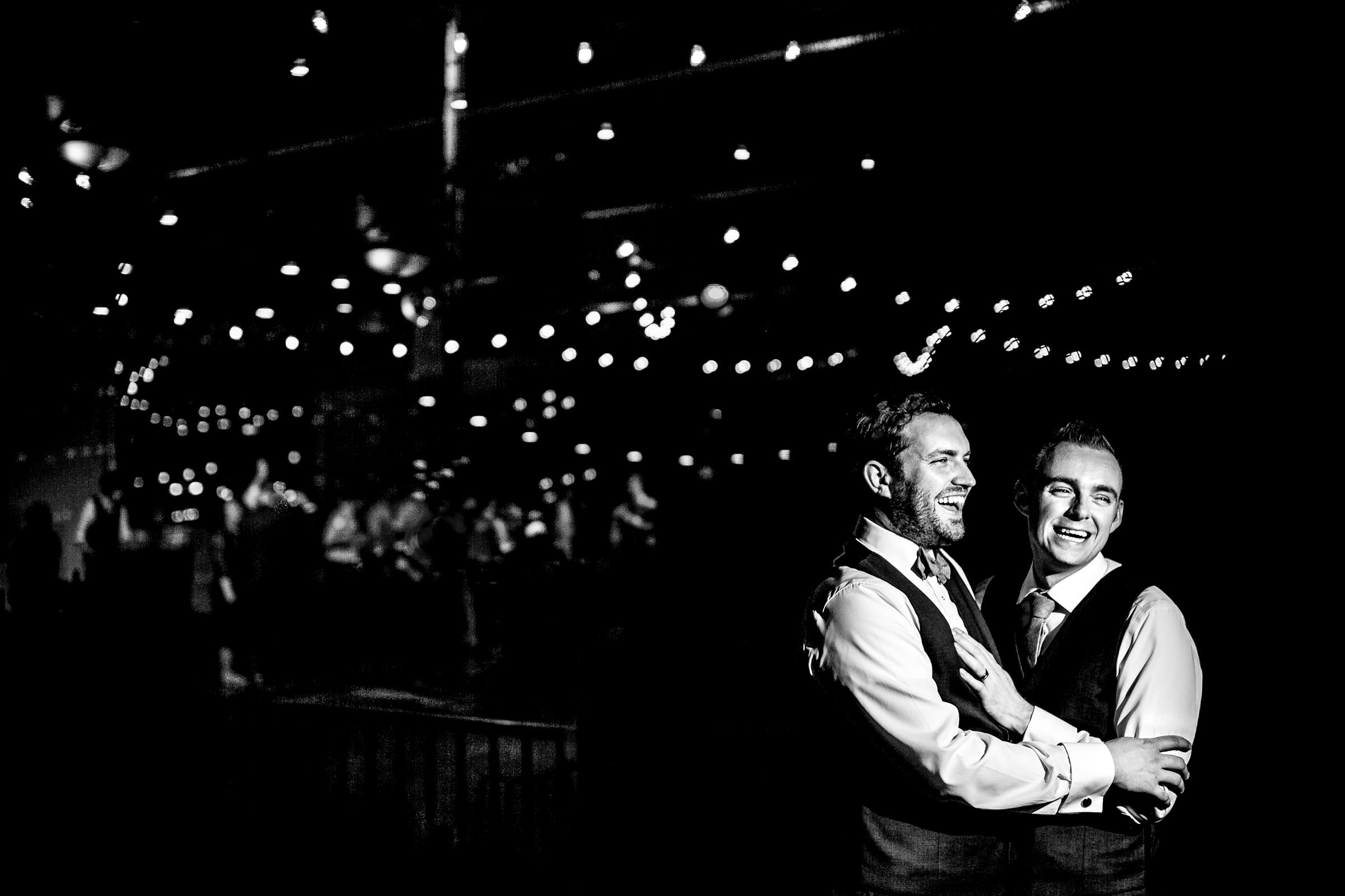Grooms laughing and holding each other during their Castaway Portland wedding reception.