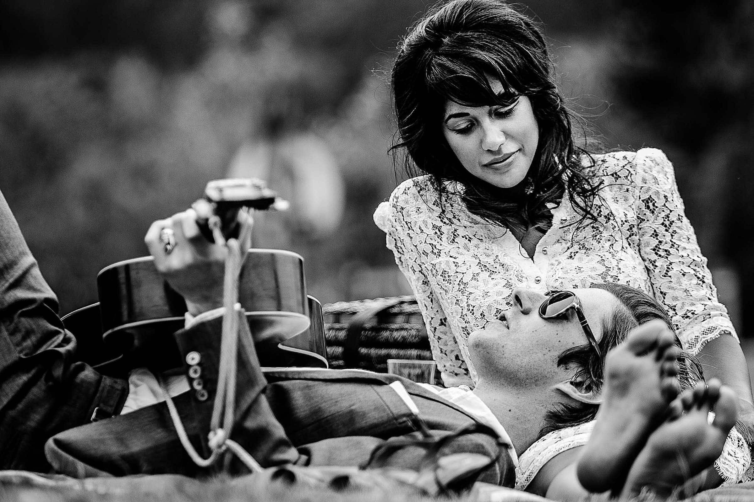 Candid beautiful engagement portrait of couple playing guitar under St Johns Bride in Cathedral Park in Portland Oregon