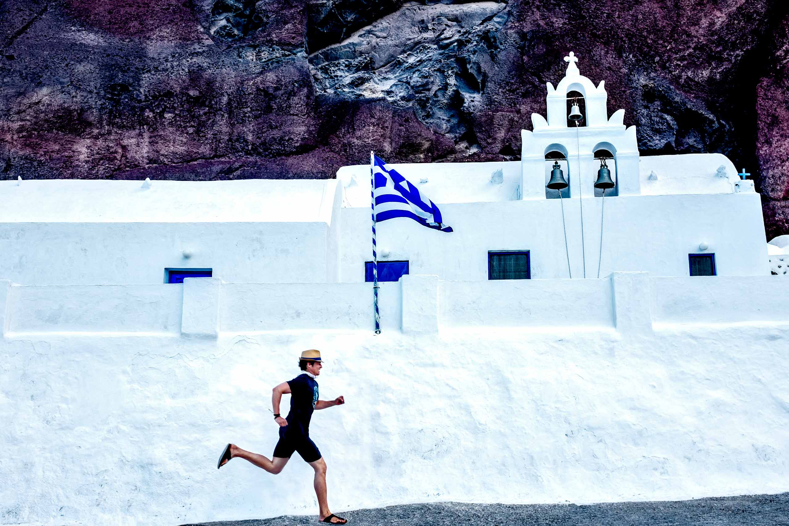 Jos WoodSmith running in Santorini Greece near a church